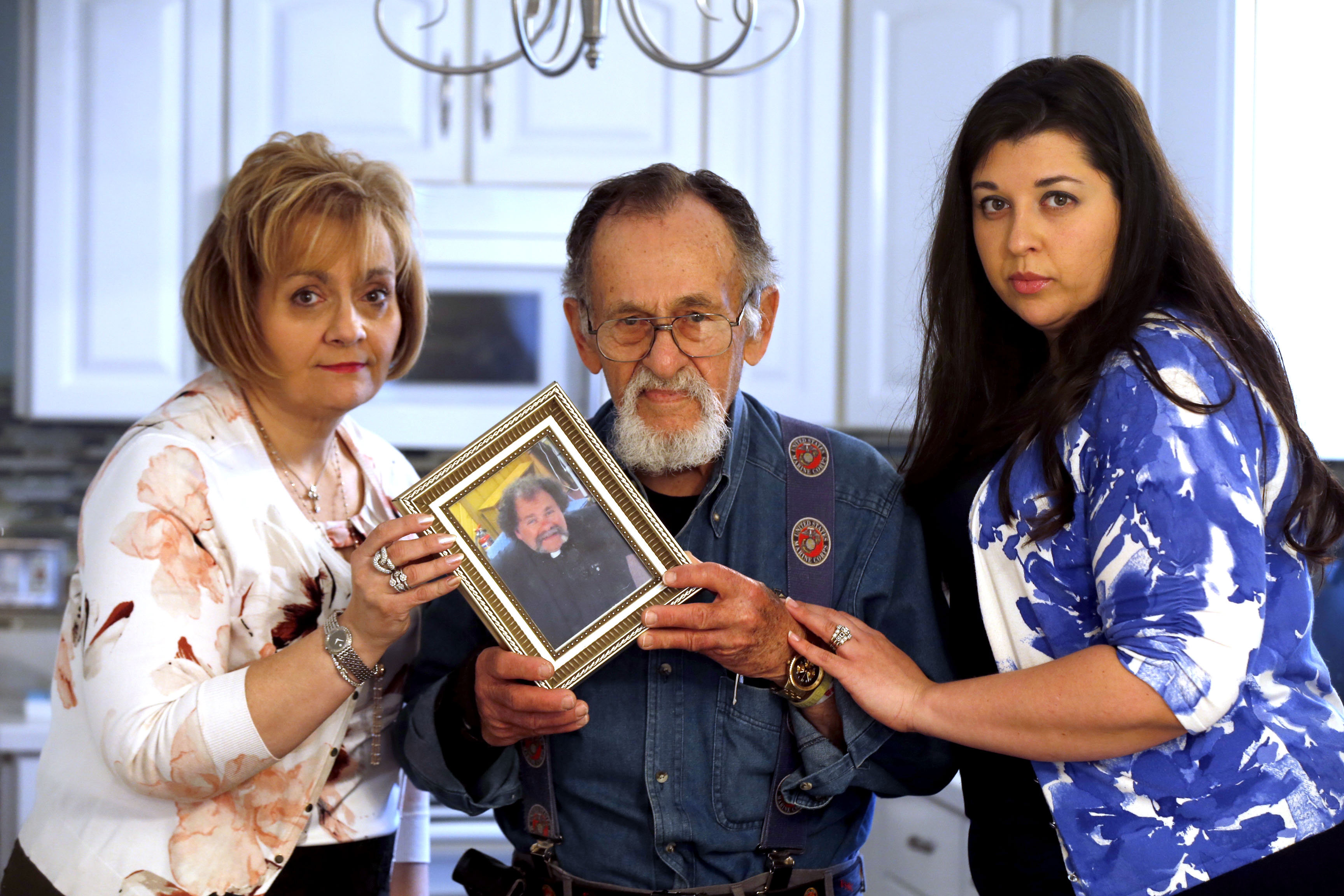 Holding a photo of Father Joe, from left, Susan M. Moreno, Joe Moreno Sr., and niece Christina Wild.  This was in Kenmore on Saturday, March 25, 2017.  (Robert Kirkham/Buffalo News)