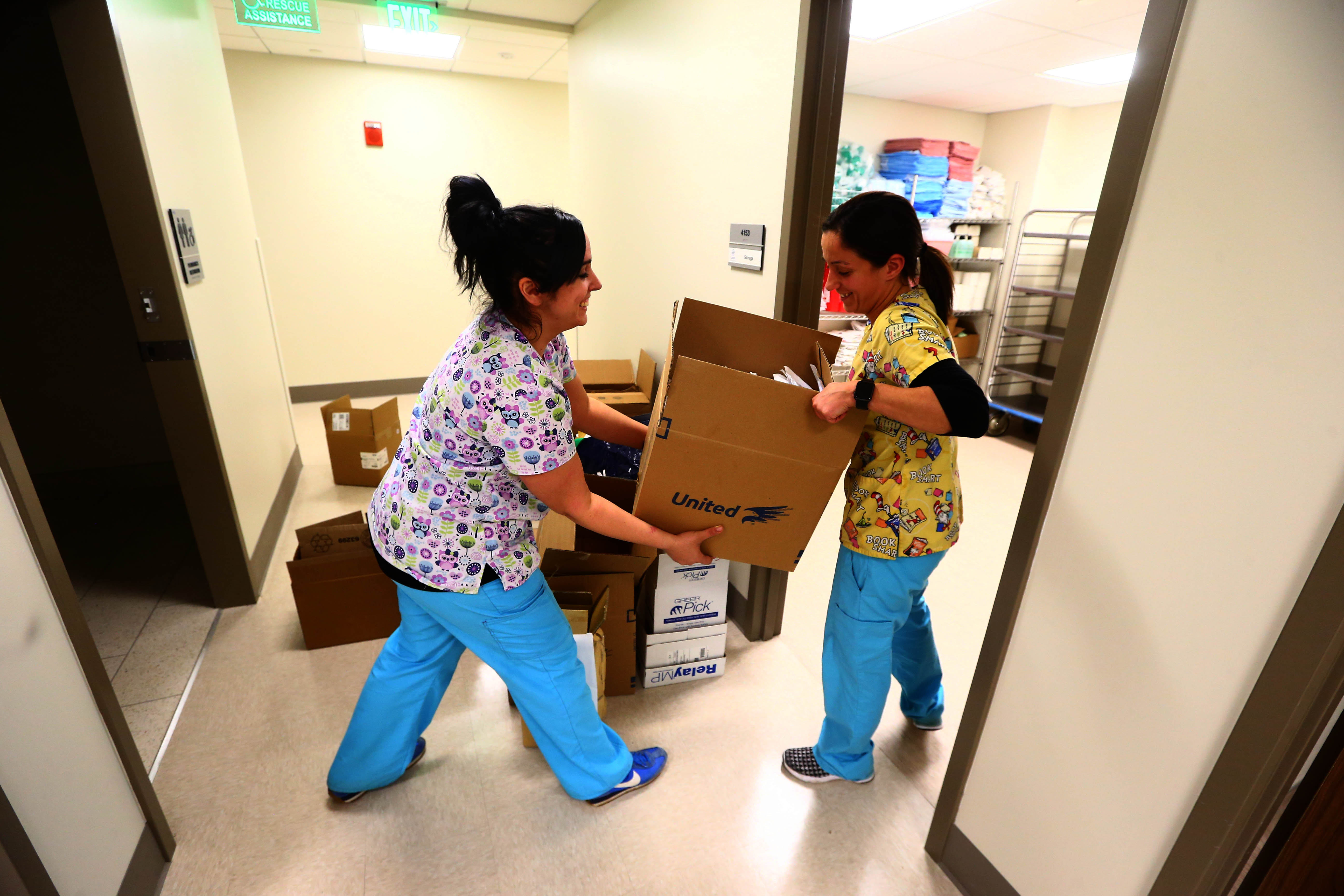 Emily Aquino, left, a registered nurse at UBMD Pediatrics, gets a hand from LPN Meghan Fusilli as they unpack supplies in a storeroom at a new pediatric clinic that opened in Conventus. (John Hickey/Buffalo News)