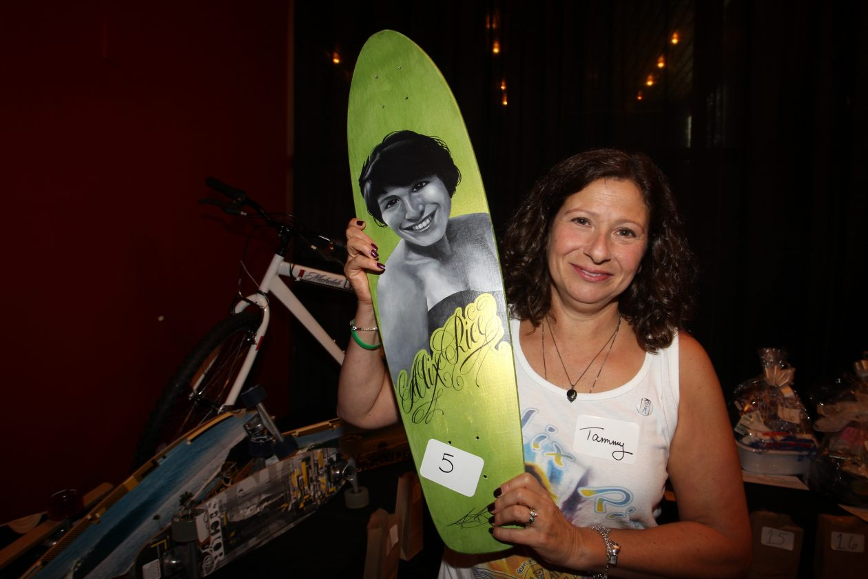 Tammy Schueler holds up a skateboard with an image of her daughter, Alexandria 'Alix' Rice, at a 2012 fundraiser for the skate park planned in her memory. That park, at the Northtown Center in Amherst, will open in August. (James P. McCoy/News file photo)