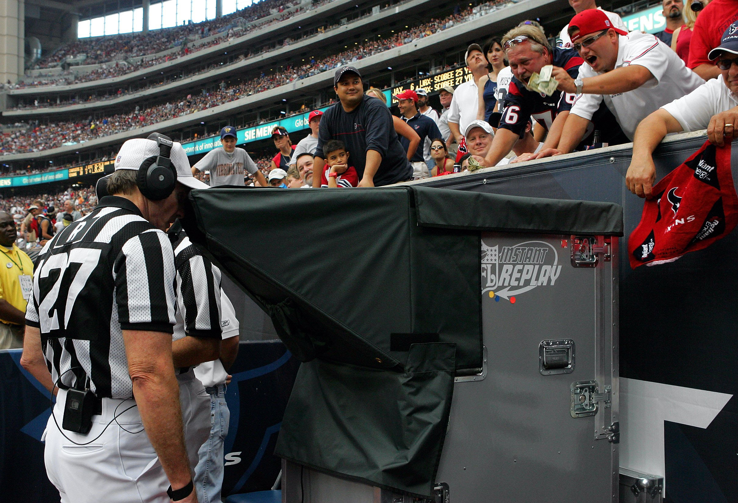 NFL referees no longer will be going under the hood to review plays. (Photo by Ronald Martinez/Getty Images)