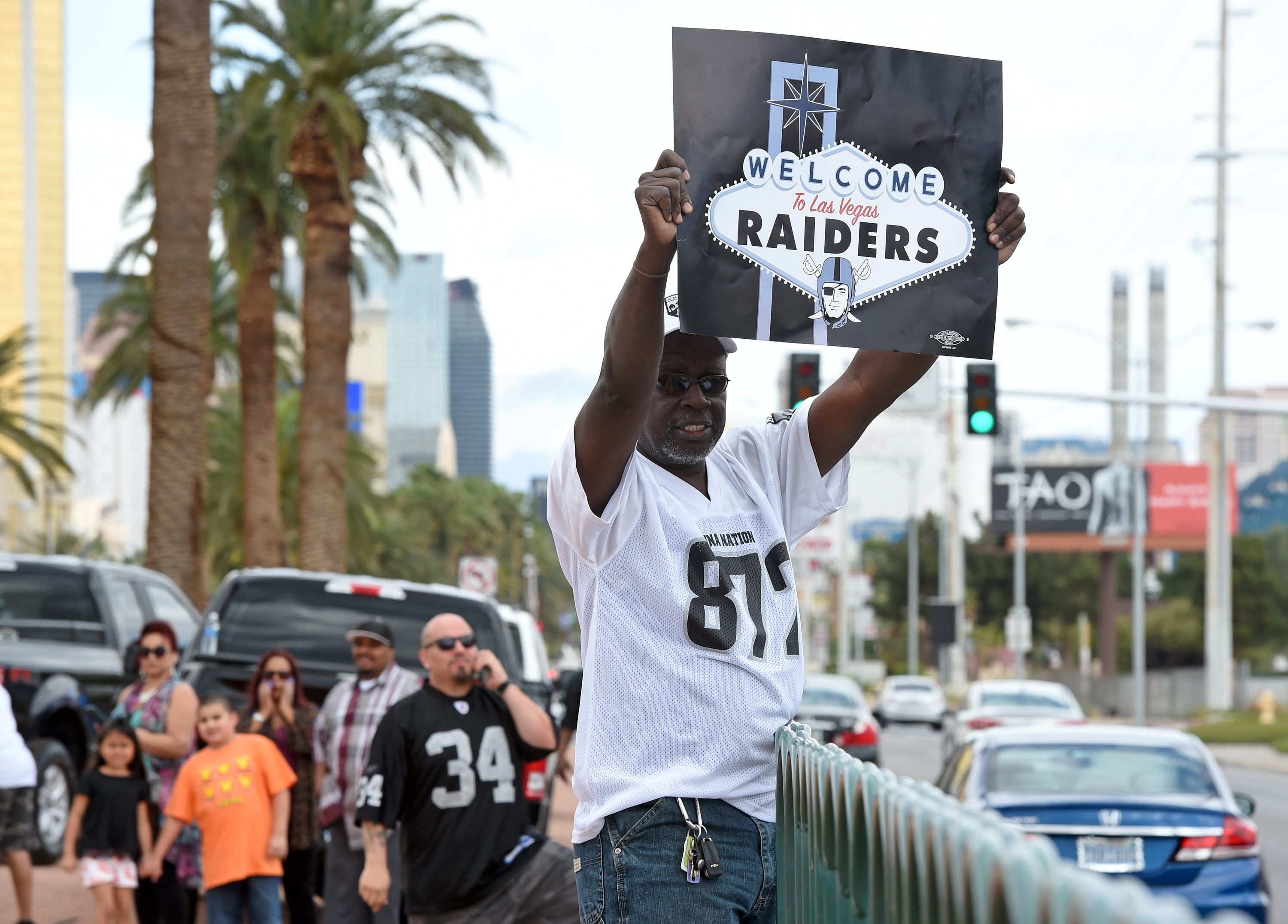 Oakland Raiders fan Davi Tole of Nevada displays a sign to passing motorists near the Welcome to Fabulous Las Vegas sign after National Football League owners voted 31-1 to approve the team's application to relocate to Las Vegas during their annual meeting. (Photo by Ethan Miller/Getty Images)