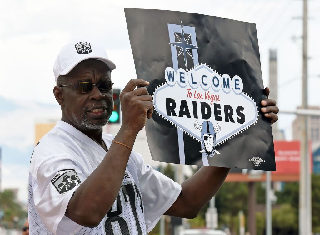 Oakland Raiders fan Davi Tole of Nevada displays a sign to passing motorists on the Las Vegas Strip near the Welcome to Fabulous Las Vegas sign after National Football League owners voted 31-1 to approve the team's application to relocate to Las Vegas during their annual meeting on March 27, 2017 in Las Vegas, Nevada.  (Getty Images)