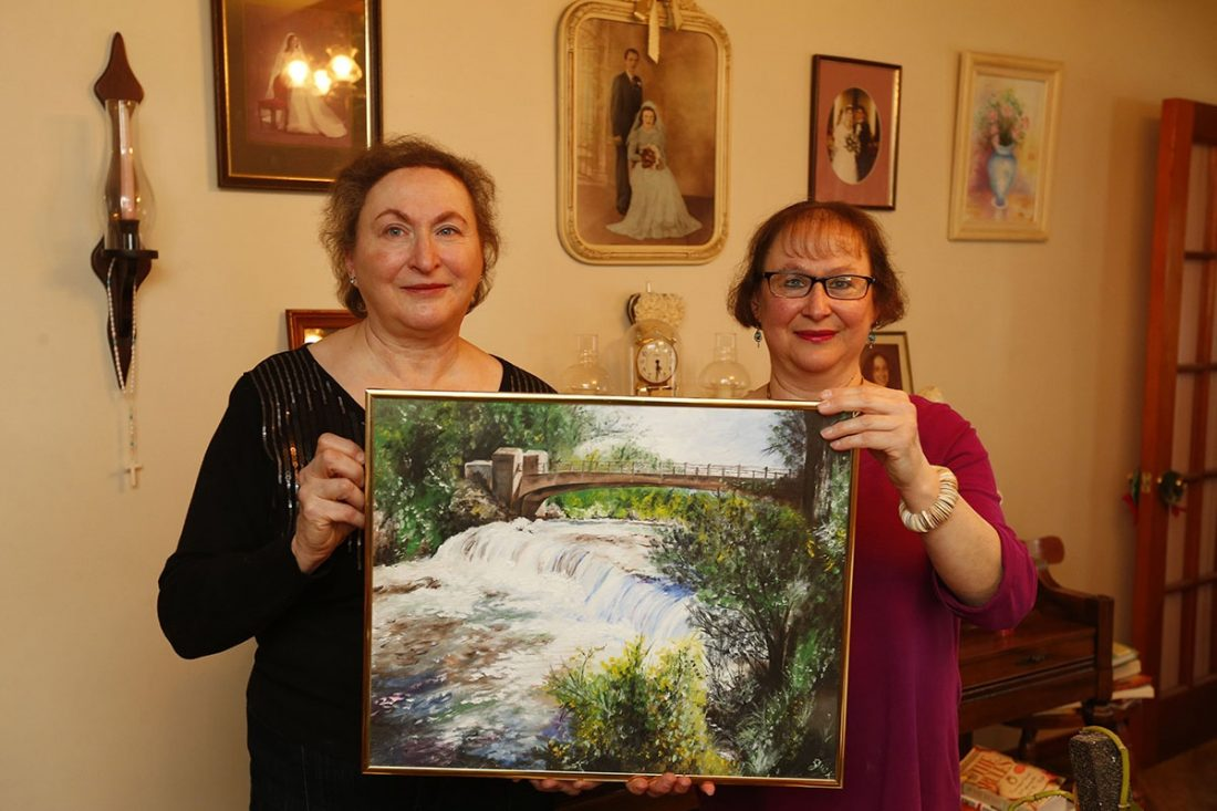 """Sisters Doris Kutlina Lucas, left, and Mary Kutlina, right, hold a painting created by their father, Joseph W. Kutlina titled, """"Three Sisters Bridge on Goat Island"""", in Niagara Falls. The image was taken in the Welch Avenue home their parents built 63 years ago. (Mark Mulville/Buffalo News)"""