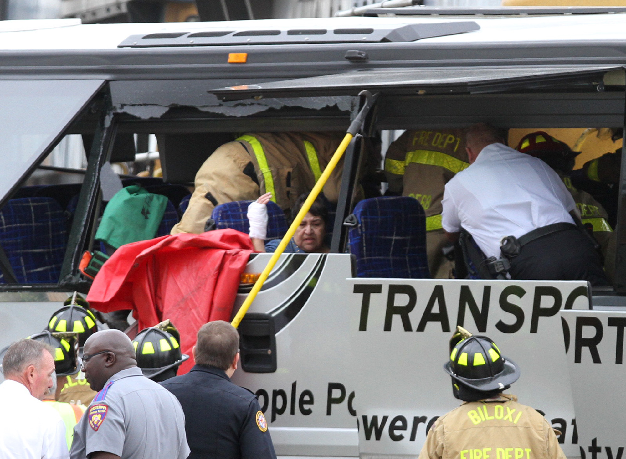 A charter bus passenger sits as rescue personnel work around her after the bus was hit by a CSX train at the Main Street crossing in Biloxi, Miss., on Tuesday, March 7, 2017. (John Fitzhugh/Biloxi Sun Herald/TNS)