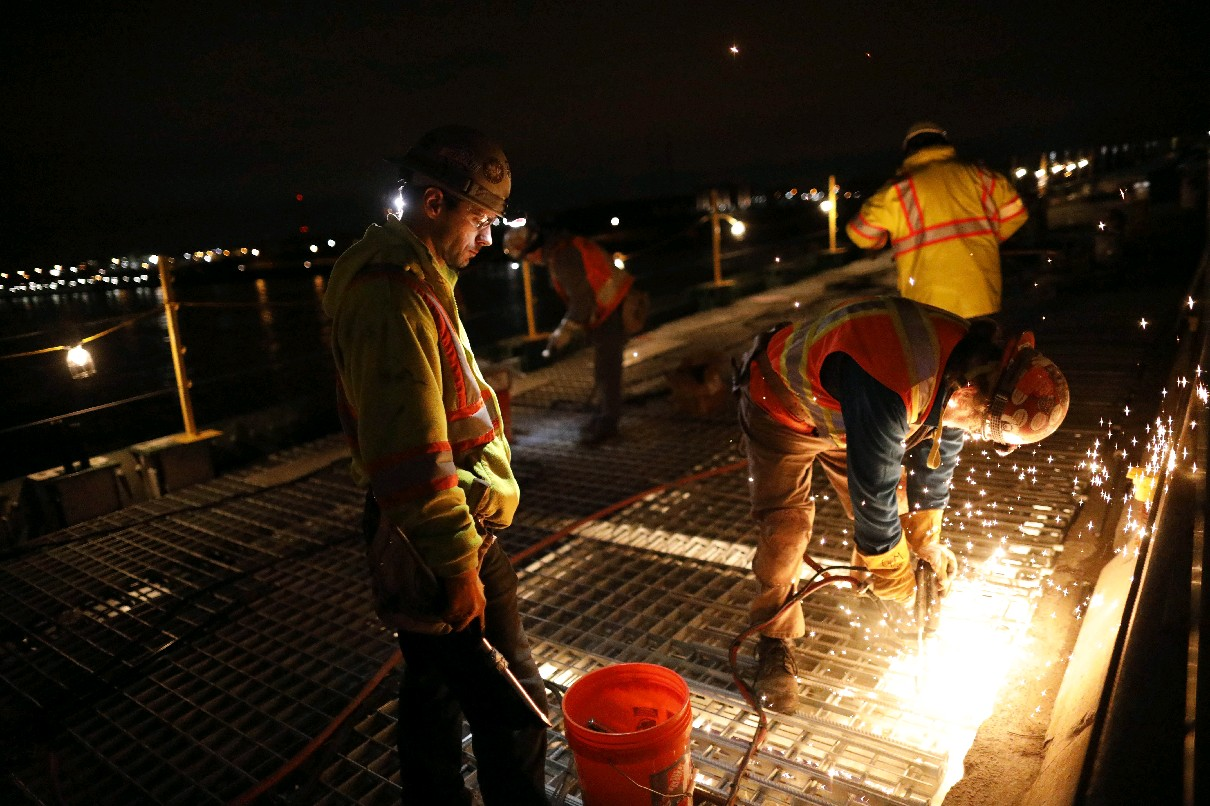 Workers weld steel grating to the frame of the Peace Bridge as part of a $100 million project designed to extend the span's life another 75 years. (Derek Gee/Buffalo News file photo)