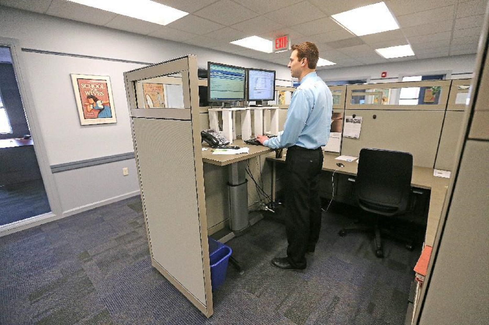 Walsh Duffield Companies employee Jon Sommer, at his standing desk, is among workers at the downtown insurance company who have benefited from the work of Wellness Team Leader Marie Story. (Robert Kirkham/Buffalo News file photo)