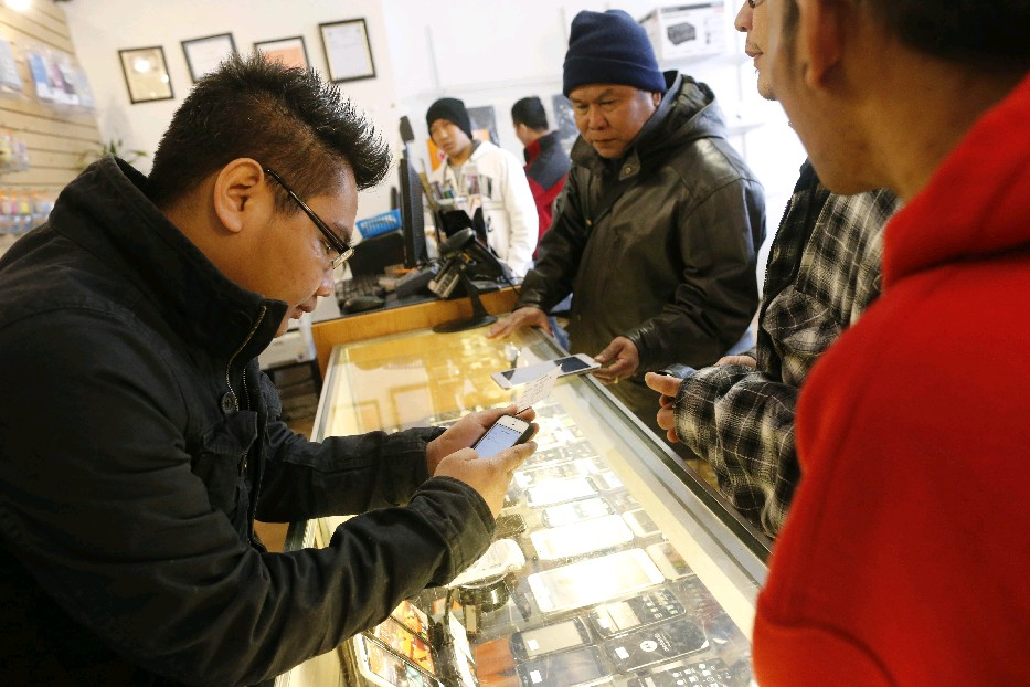 iT Garden owner Aung Kaung Myat, who fled here from Burma, helps  Burmese customers purchase a new cell phone. His Grant Street shop is the type of business advocates say refugees add to the local economy. (Derek Gee/News file photo)