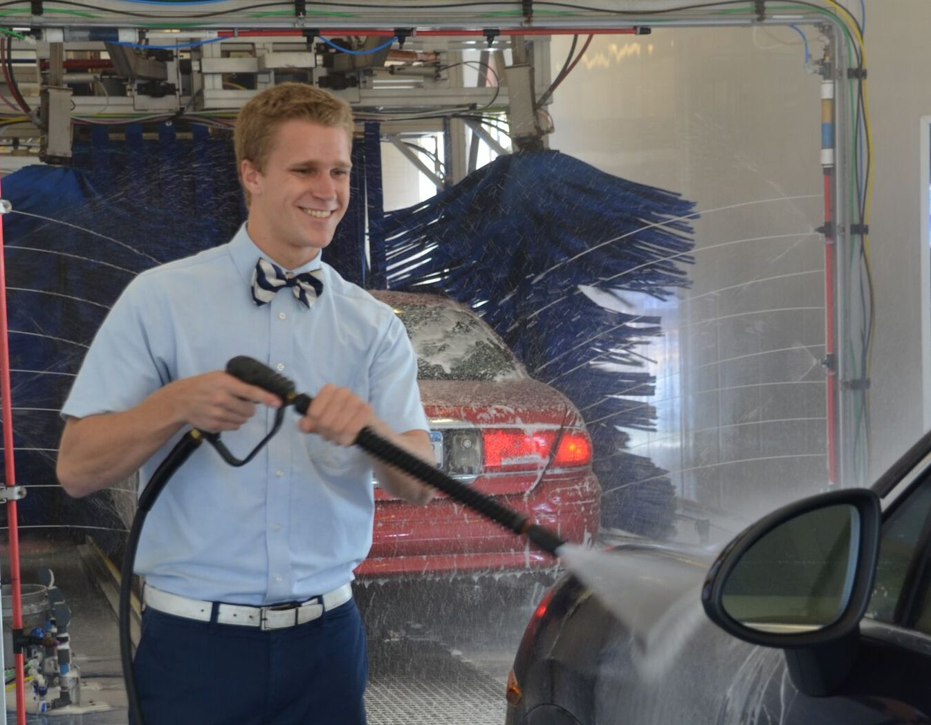 Alex Leszczynski  sprays a car at Royal Car Wash's Monroe location in Greece. (Contributed photo)