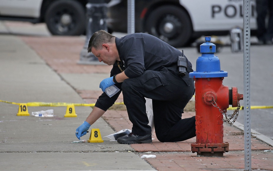 A Buffalo police crime scene investigator marks and collects spent handgun shells that were scattered around a baseball cap that fell from one of the people involved in Monday afternoon's shooting. (Robert Kirkham/Buffalo News)