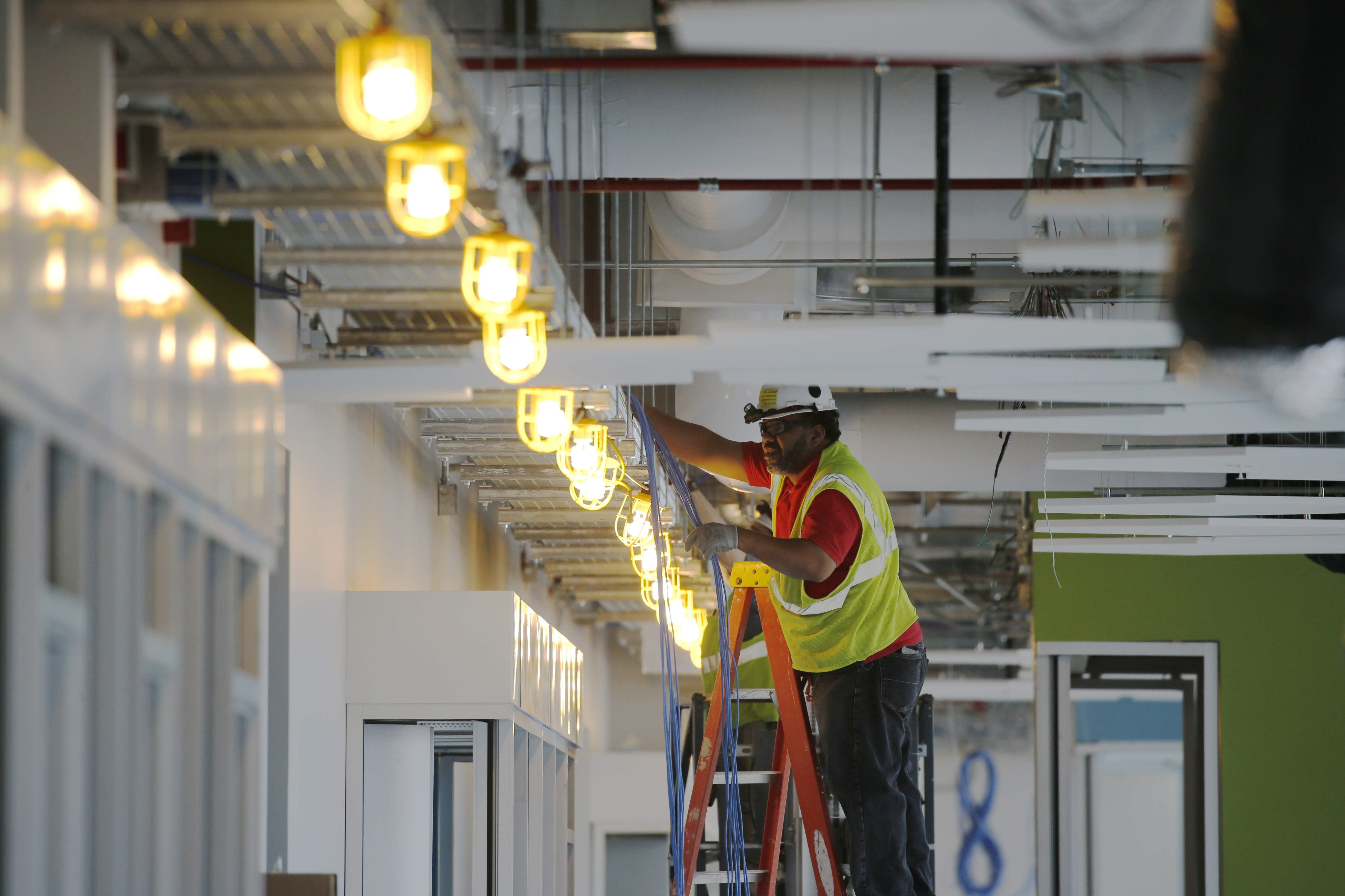 An electrician runs wire in the office area as construction continues at the massive Solar City manufacturing facility at RiverBend in a file photo from May 2016.  (Derek Gee/Buffalo News file photo)
