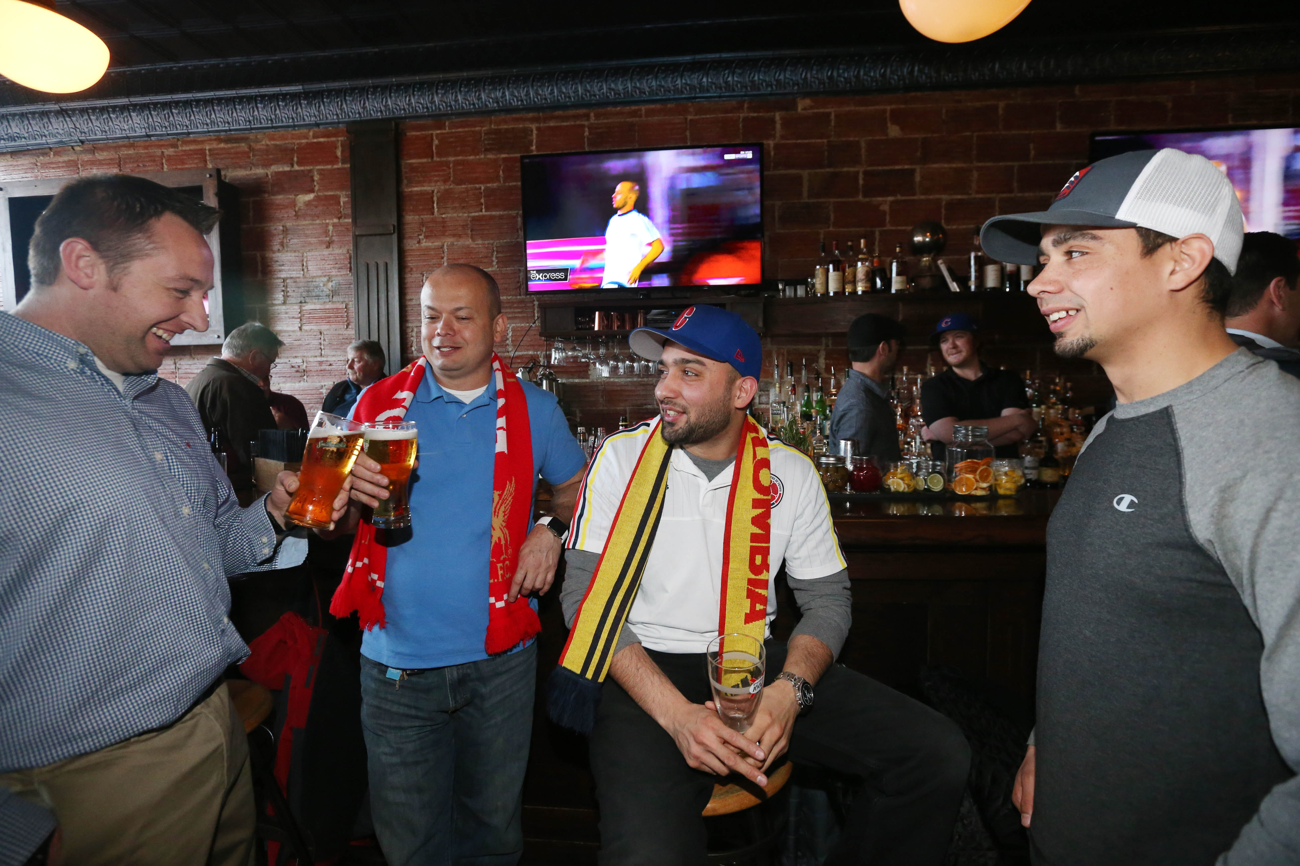 Soccer fans Dan Scott, left, Miguel Salazar, Andres Paehy and Glen Friot hang out recently at Mes Que. (Sharon Cantillon/Buffalo News)