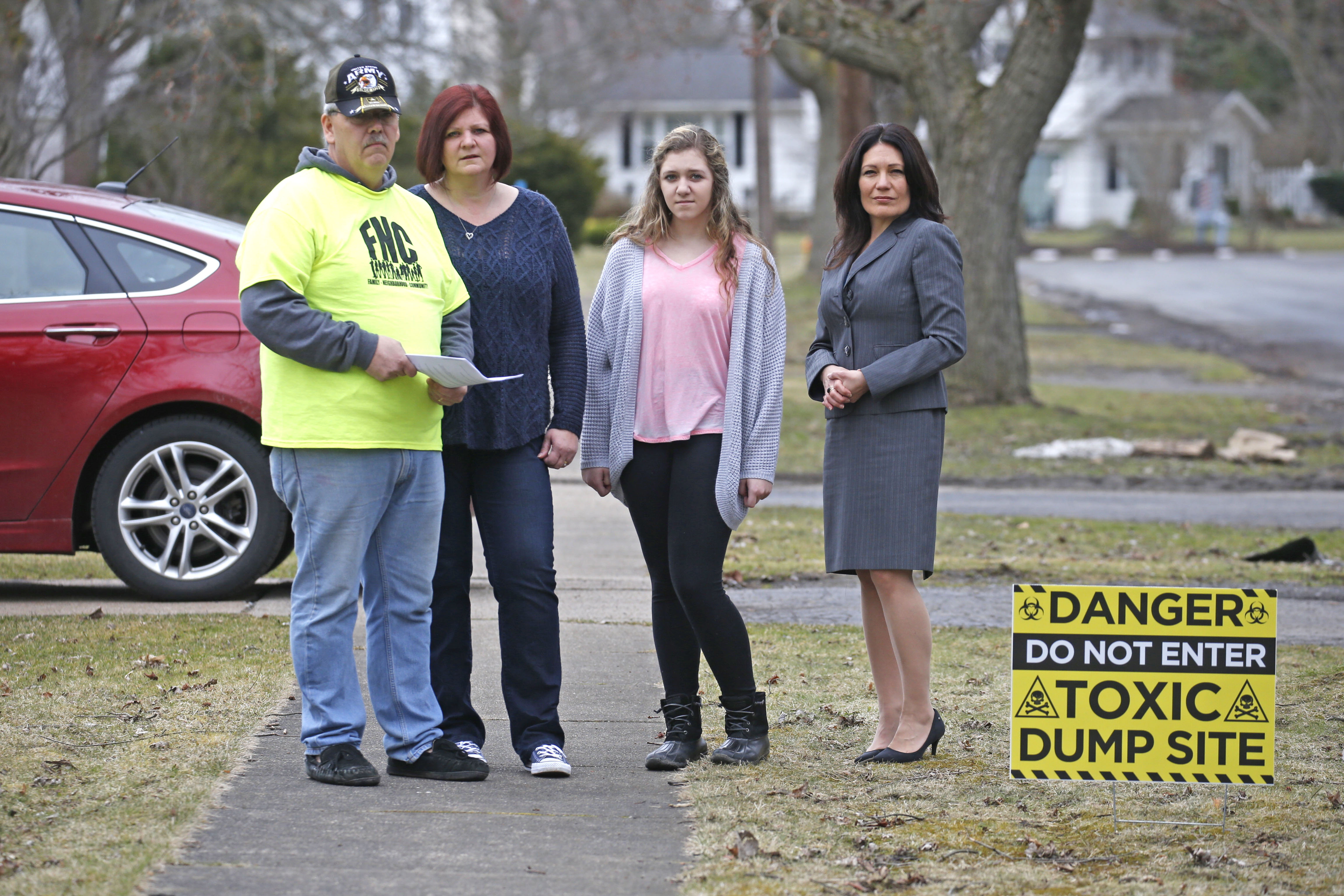 Next to a sign on the Grawe Family's lawn in North Tonawanda are from left, Brett, wife Becky and daughter Samantha with environmental attorney Christen Civiletto on Tuesday, March 28, 2017.  (Robert Kirkham/Buffalo News)