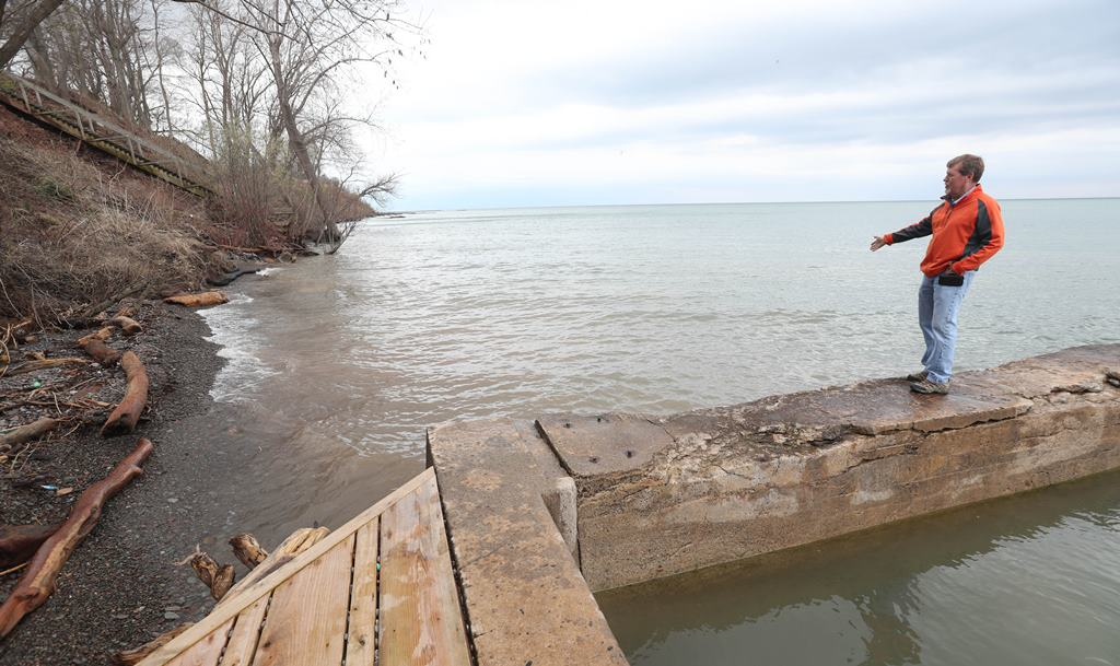 Al Weir  stands on the pier where the beach used to extend at his house on Lake Ontario in Burt.  He's never seen the water so high.   (Sharon Cantillon/Buffalo News)
