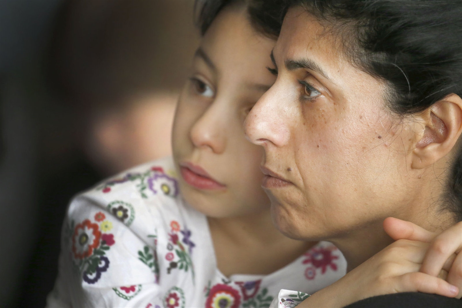 Michal Lewis and her daughter Sarah, 8, listen as the list of concentration camps is read during Sunday's commemoration at Temple Beth Tzedek in Amherst. (Robert Kirkham/Buffalo News)