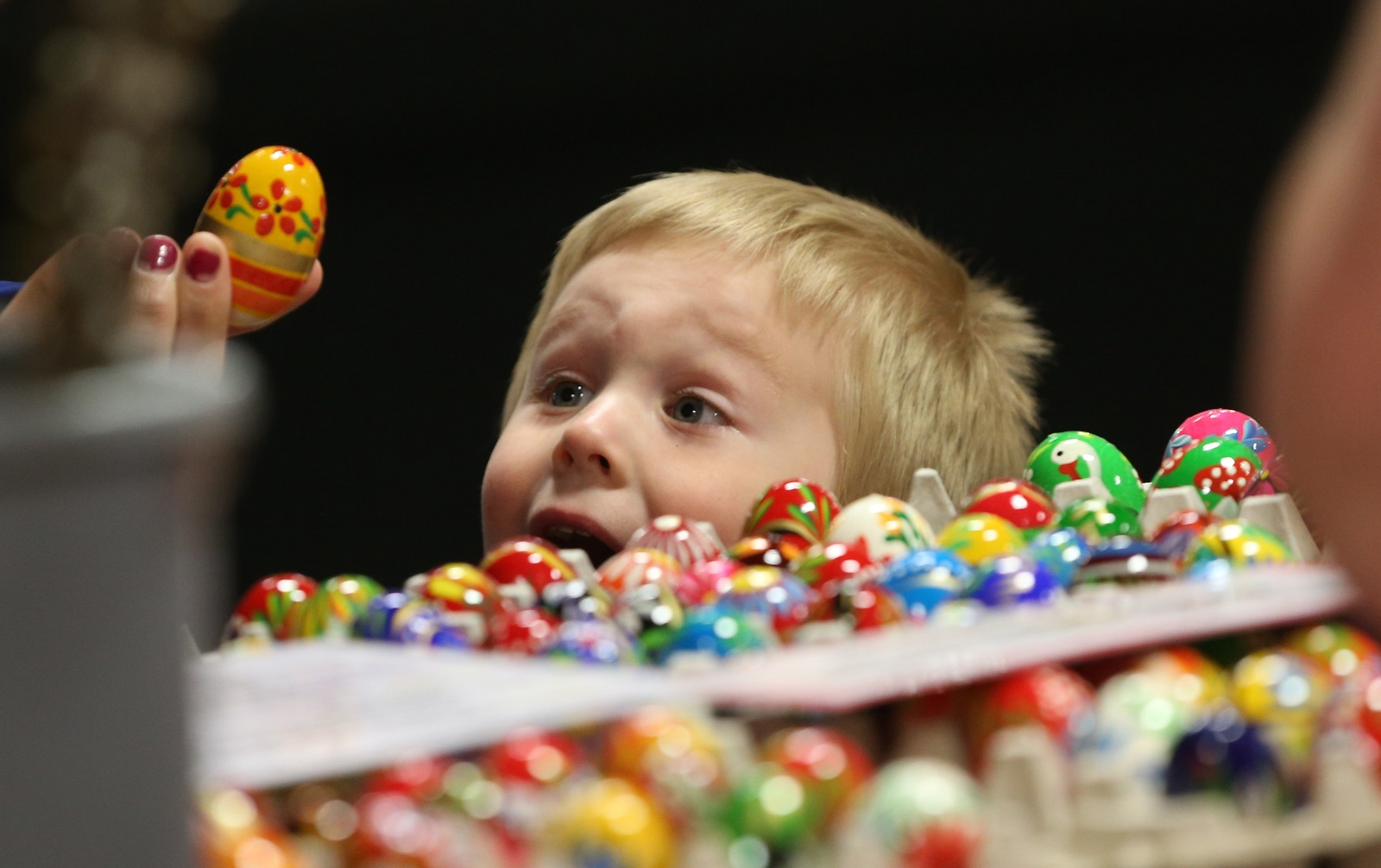 Kyle Michalek, 3, gets excited about picking out some Polish wooden eggs with his mom at Lewandowski Produce in the Broadway Market.  (Sharon Cantillon/Buffalo News)