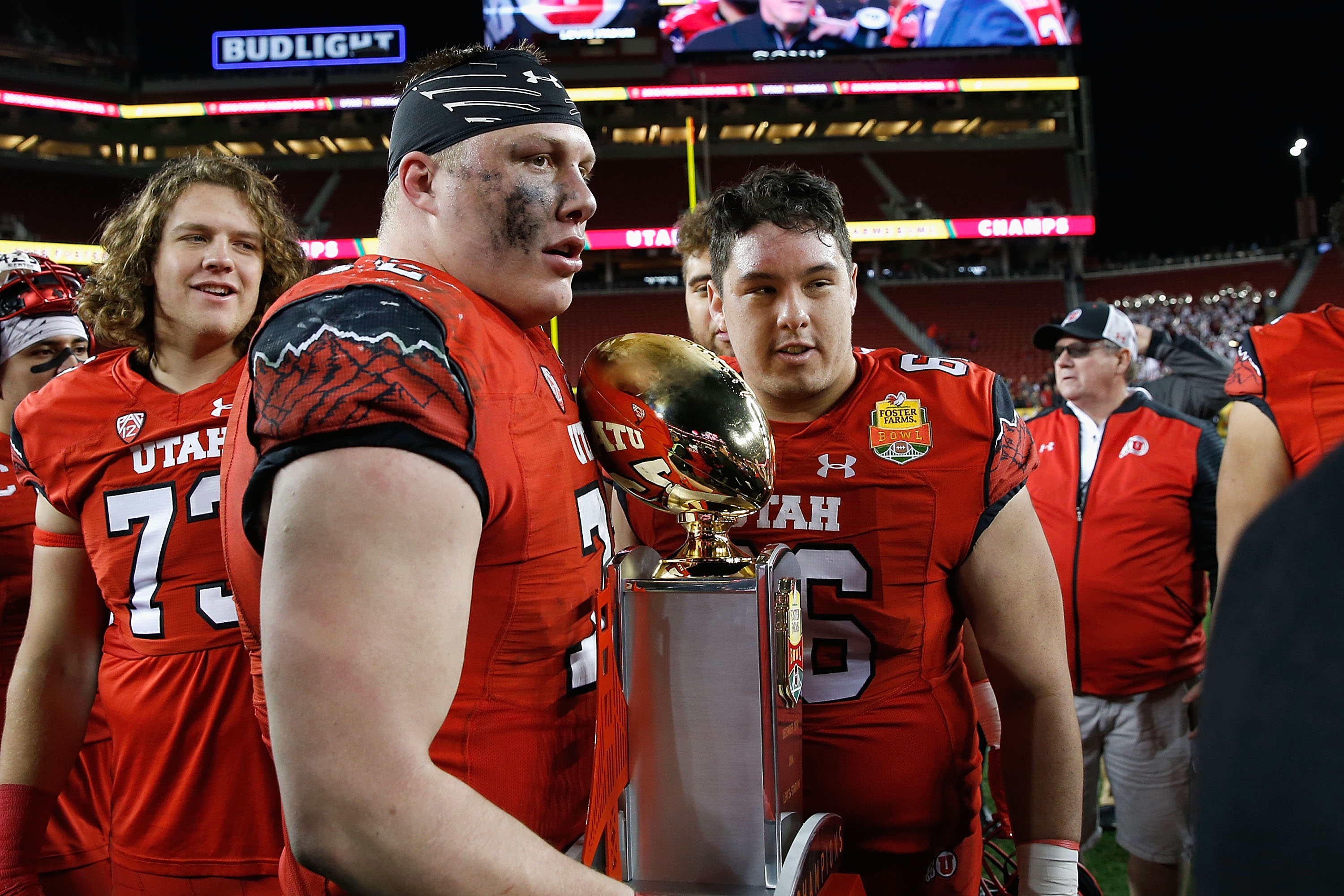 Garett Bolles, center, of the Utah Utes with the trophy after a win against the Indiana Hoosiers in the Foster Farms Bowl game on December 28, 2016. (Photo by Lachlan Cunningham/Getty Images)