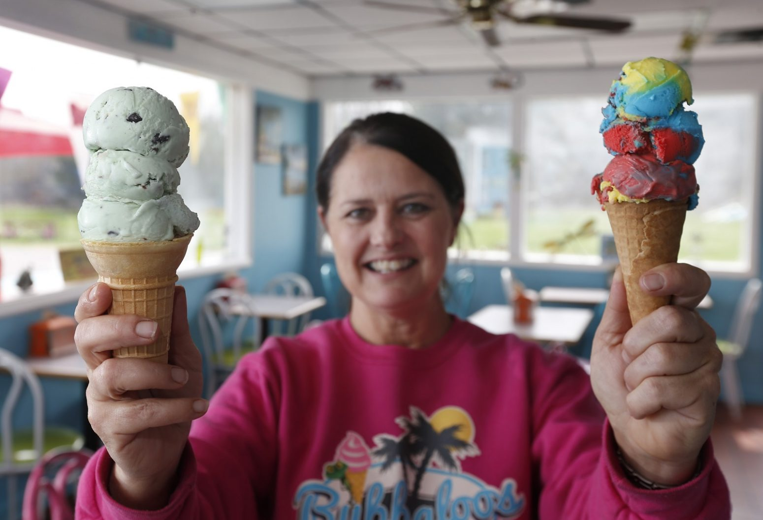Perry's has more than 300 associates who sell their ice cream. One is Bubbaloos on Main Street in Akron. Owner Brenda Schlager shows off the popular Mint-Ting-A-Ling and Super Hero cones. (Sharon Cantillon/Buffalo News)