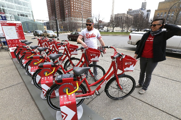 Reddy Bikeshare fleet manager Nathan Schultz and employee Jennifer White do a final check on bikes in their docking station in front of City Hall as the program's second season kicked off Monday. (Robert Kirkham/Buffalo News)