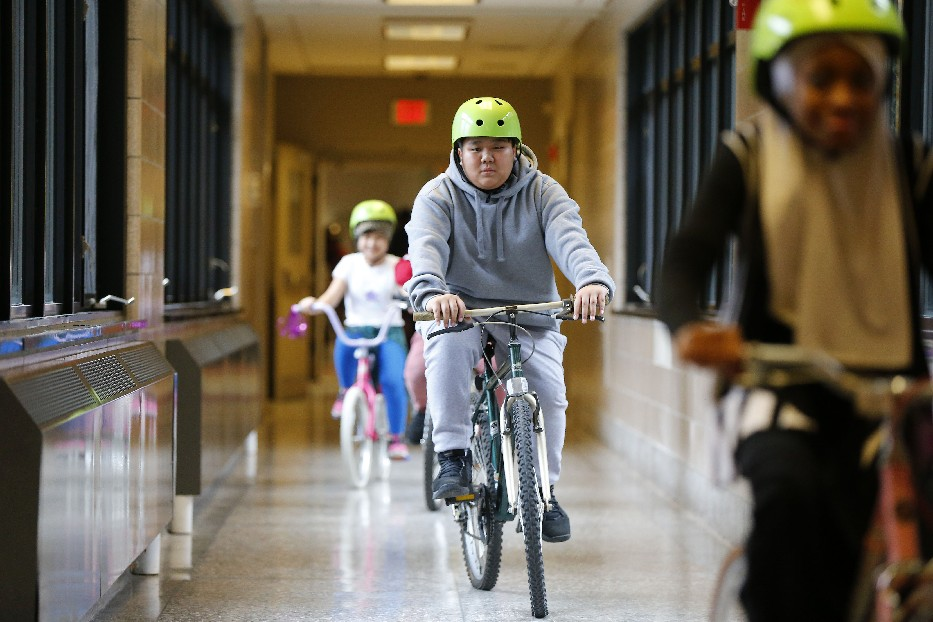 International School 45 student Me Reh takes a spin in the hall on the used bike he rebuilt in an after-school program. (Mark Mullville/Buffalo News)