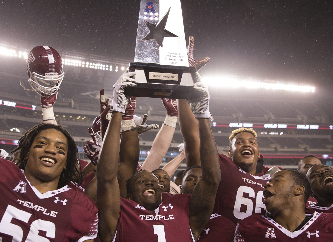 Dion Dawkins (66) and Temple teammates celebrate with the American Conference East Division trophy after defeating Connecticut. (Getty Images)