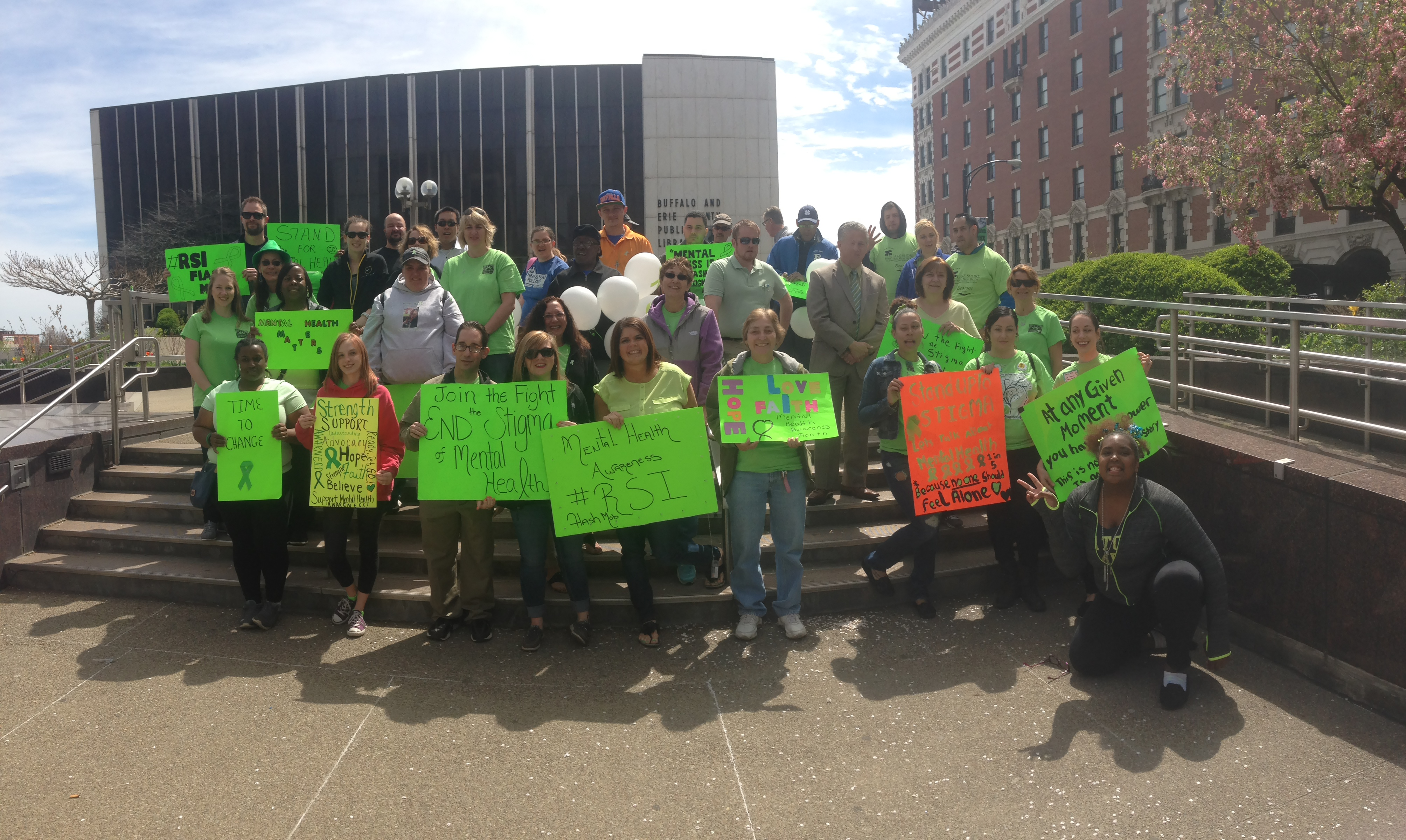 The annual Mental Health Awareness Informational Fair and Flash Mob is designed to help raise awareness about mental illness in WNY, and provide resources for families touched by it, says Michelle Scheib, center, with the 'Mental Health Awareness' sign. This year's event will take place Thursday at the Central Library.