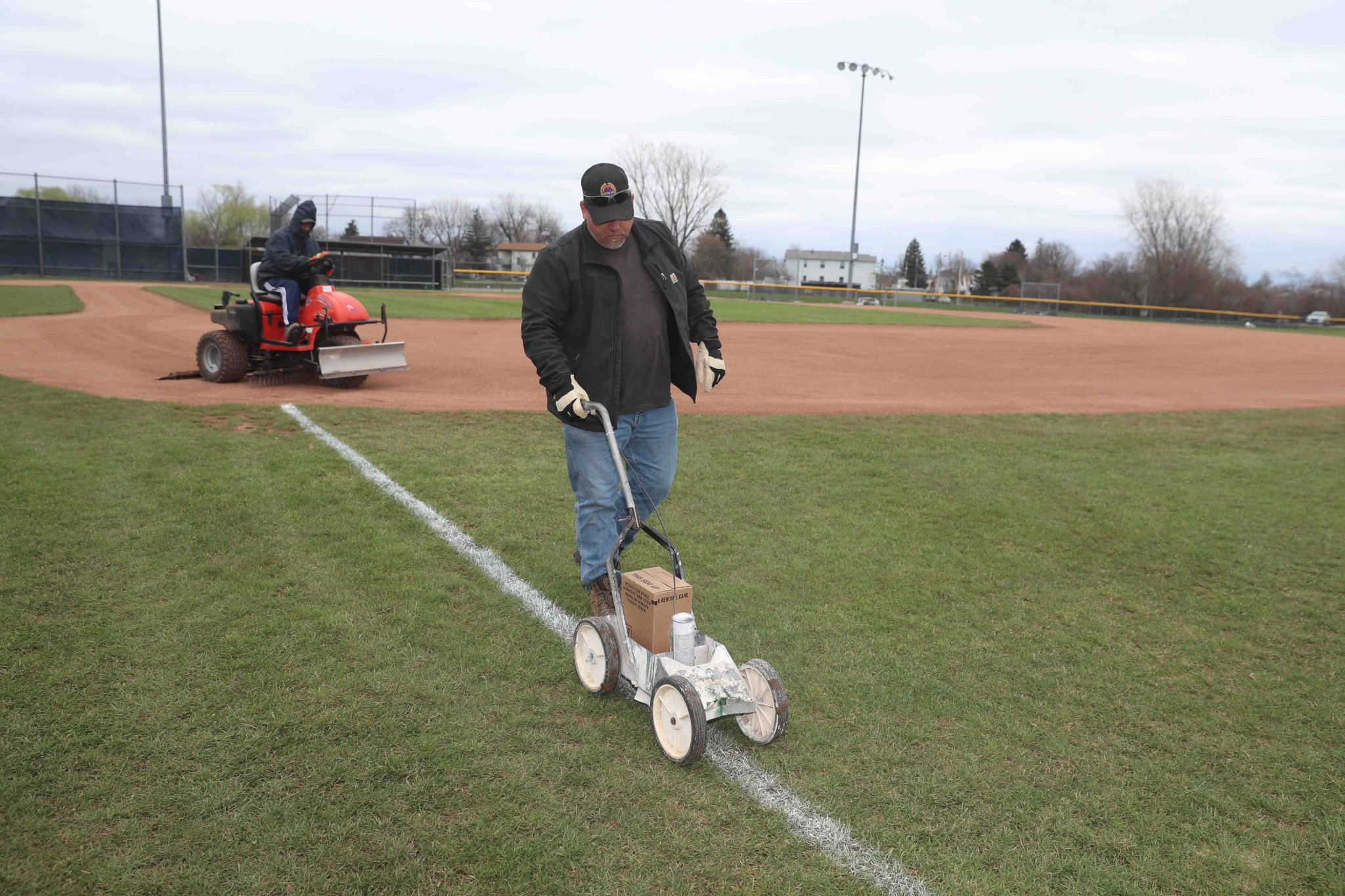 Buffalo Parks Utility worker Paul Snyder restripes lines while Kenneth Stevens grooms the diamond at McCarthy Park ball field. (John Hickey/Buffalo News)