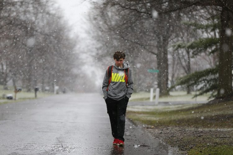 Sean Kane walks home from school as puffy snowflakes start to fall in Orchard Park last week. The first snows of April will come later tonight, the National Weather Service advises. (Mark Mulville/Buffalo News)