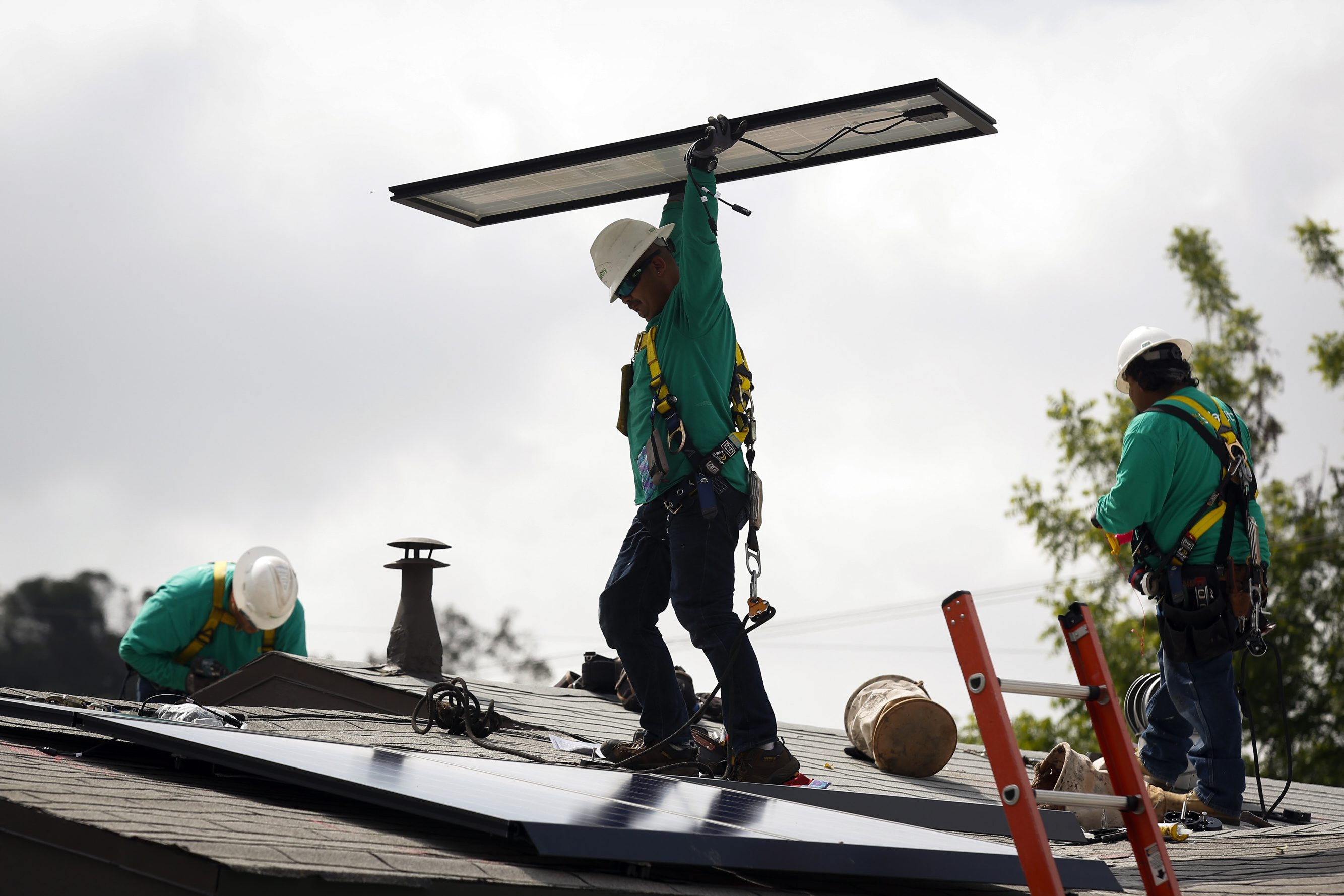 A SolarCity employee carries a solar panel being installed on the roof of a home. (Bloomberg file photo)