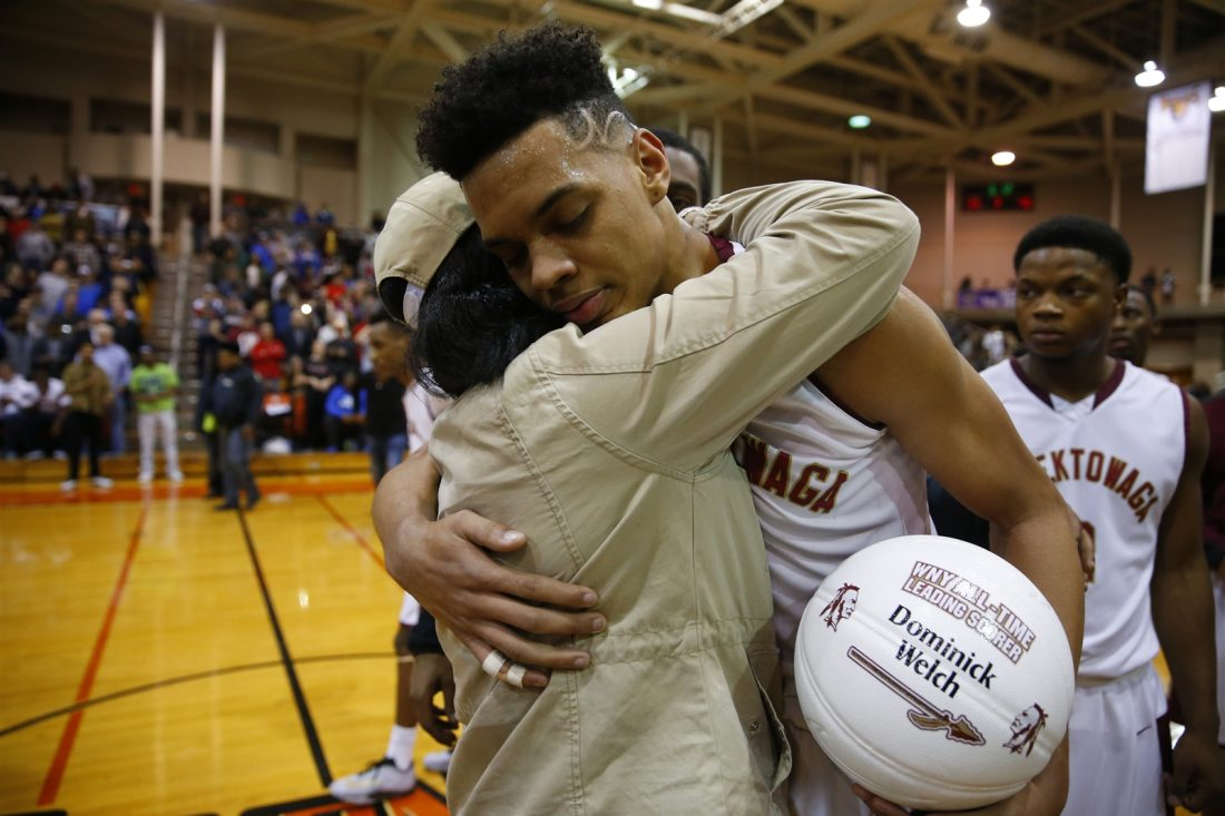 Cheektowaga's Dominick Welch receives a hug after breaking the Western New York boys basketball scoring record during the Warriors' final game of the 2017 season. (Harry Scull Jr./Buffalo News)