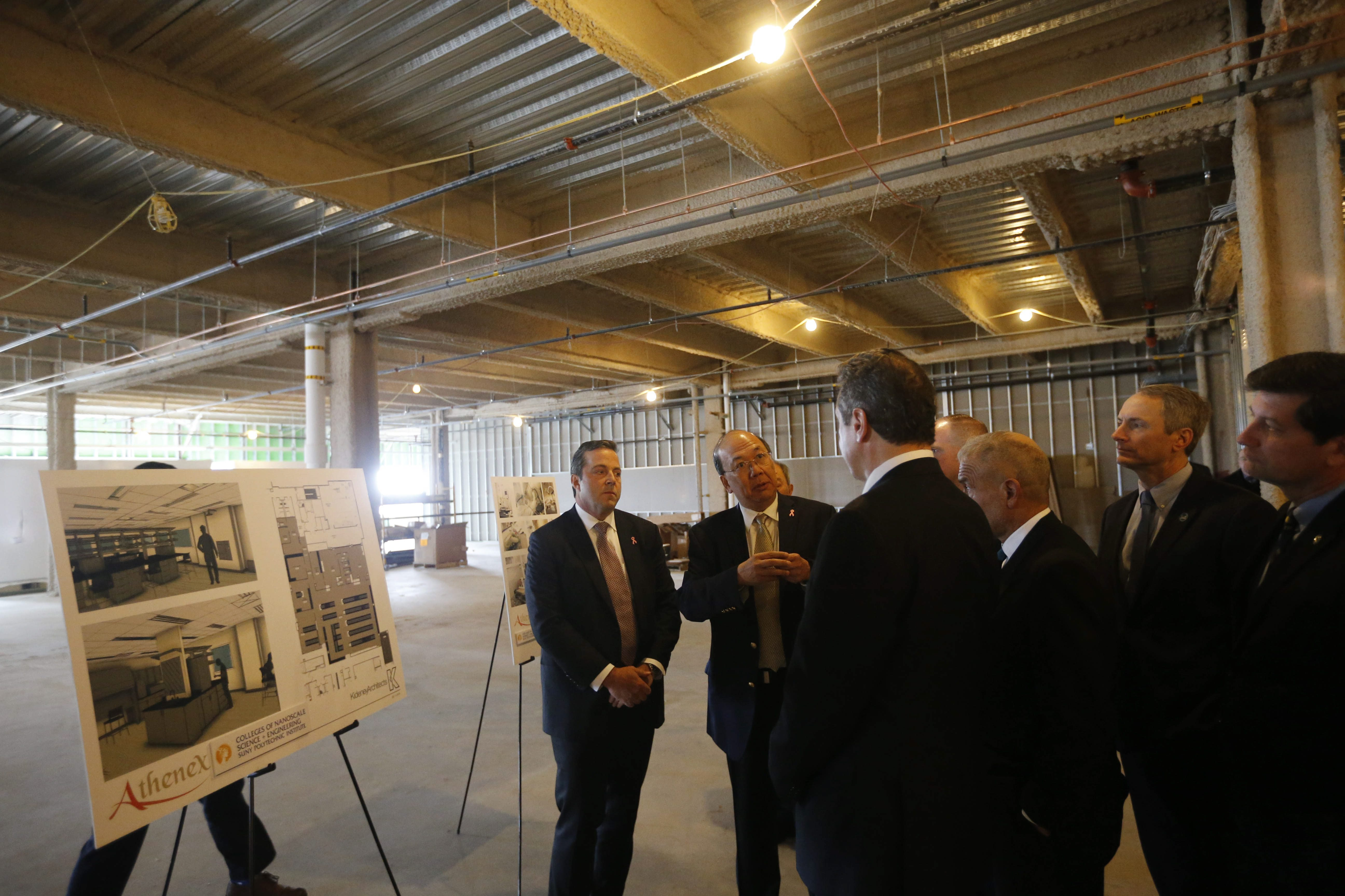 Athenex CEO Johnson Y. N. Lau, center, speaks with Gov. Andrew Cuomo and Assemblyman Sean Ryan during a construction tour of the new Athenex facility at Conventus in 2016. Also shown is Flint D. Besecker, left, who was then Athenex COO and CFO. Besecker has since left the company. (Derek Gee/Buffalo News)