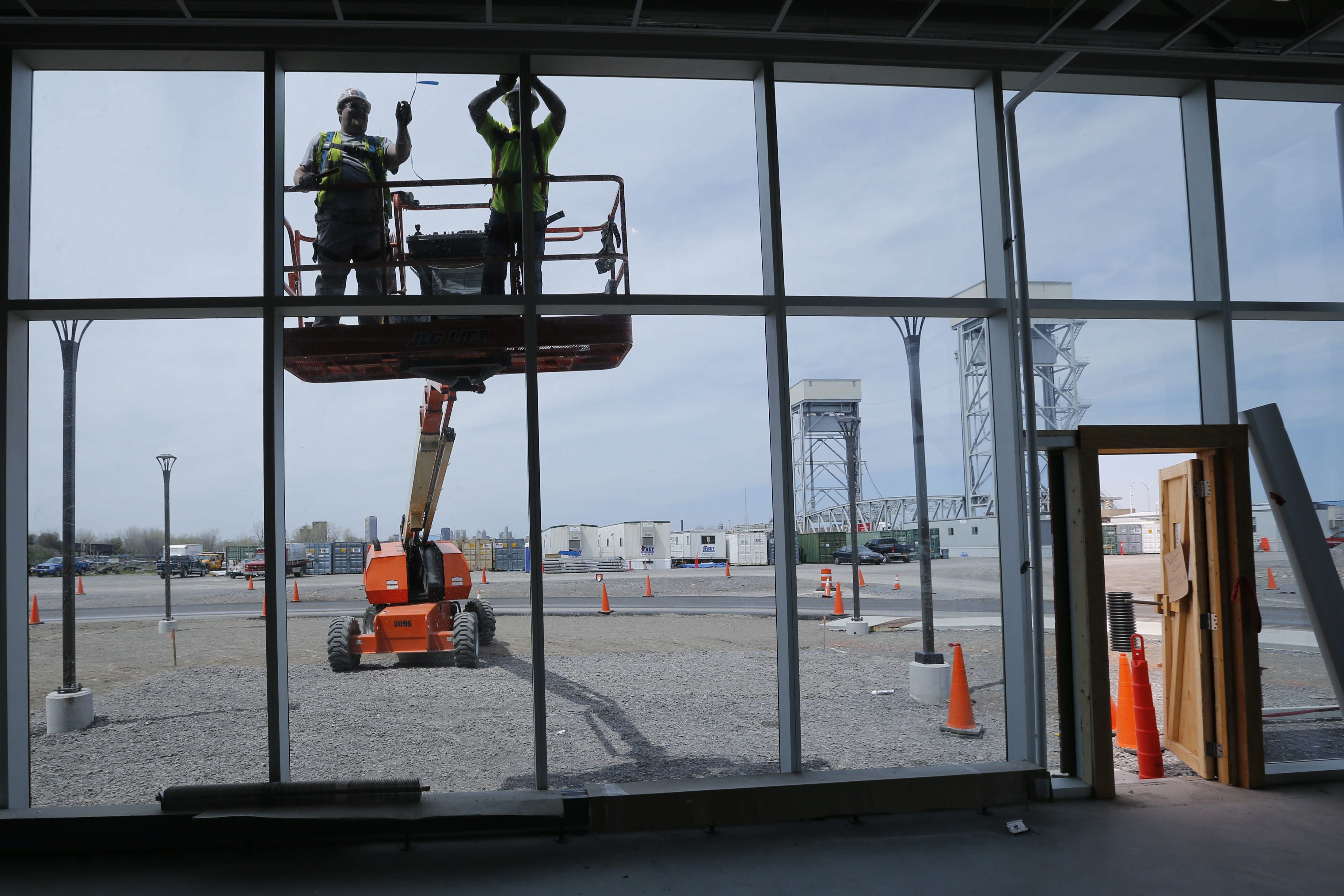Workers weatherproof the glass facade of the offices at the massive SolarCity manufacturing facility at RiverBend in May 2016. The factory is now largely complete and awaiting production. (Derek Gee/Buffalo News file photo)