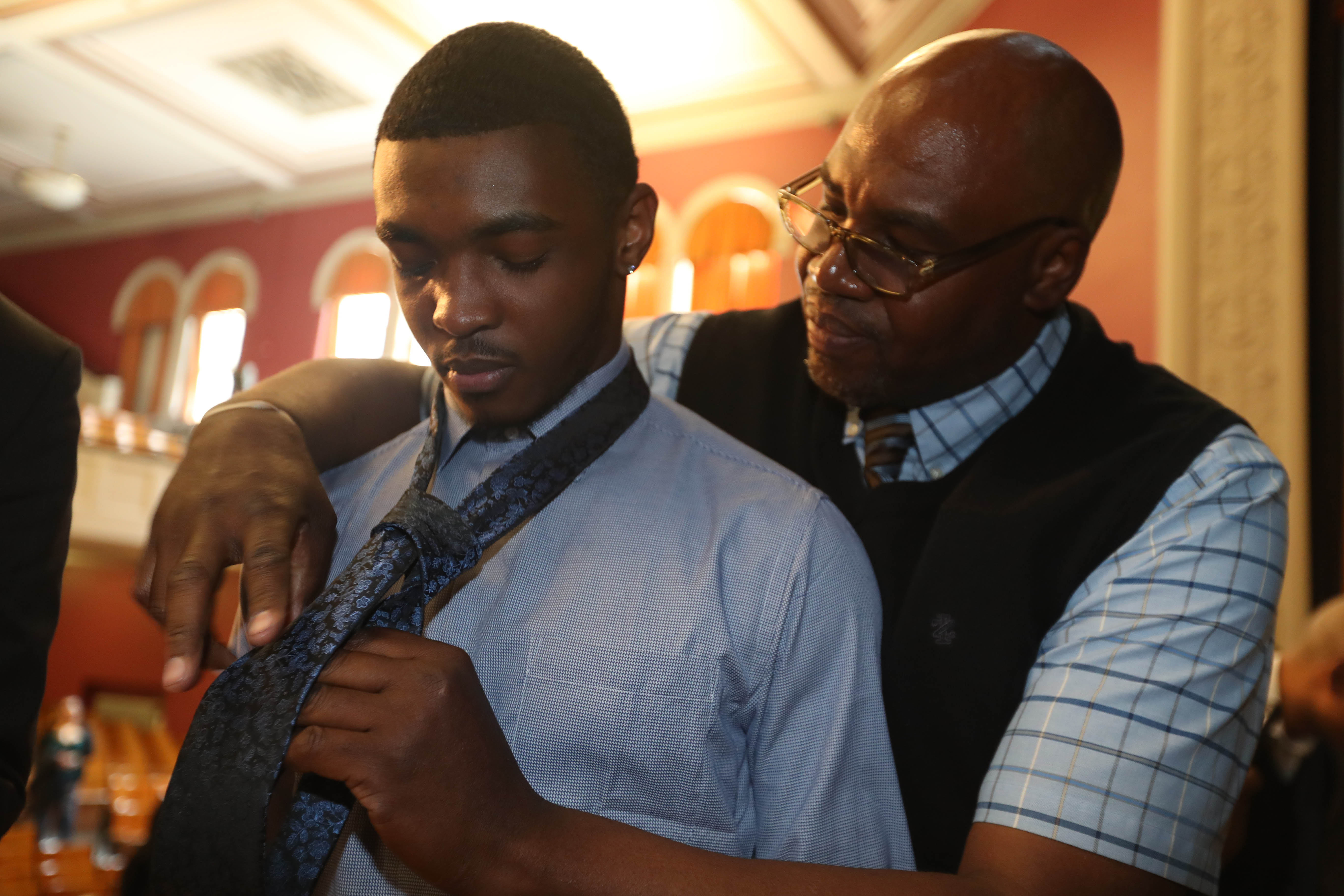 Helping Families and Children of America hold the Boys to Men Youth Empowerment Conference at East High, Saturday, May 13, 2017. Murray Holman, right, of Stop the Violence Coalition shows Isaiah Lee, of Burgard High School, how to tie a tie.  (Sharon Cantillon/Buffalo News)