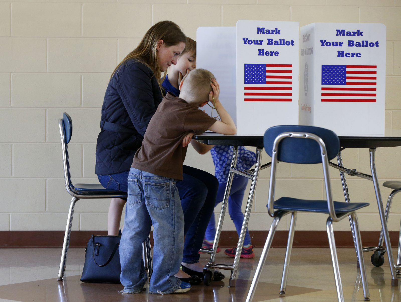 Jennifer Mumm votes with her children Griffin, left, Connor, right, and Kate, hidden, at East Aurora Middle School on Tuesday, May 16, 2017. (Mark Mulville/News file photo)