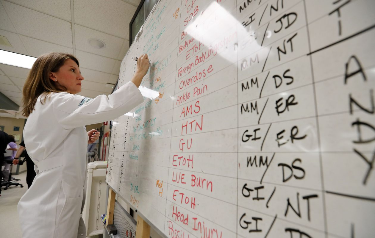 Dr. Jennifer Pugh writes on the white board used in the Emergency Department at ECMC.  This is the same board they used when the hospital's computer network was attacked a few weeks ago.           (Mark Mulville/Buffalo News)