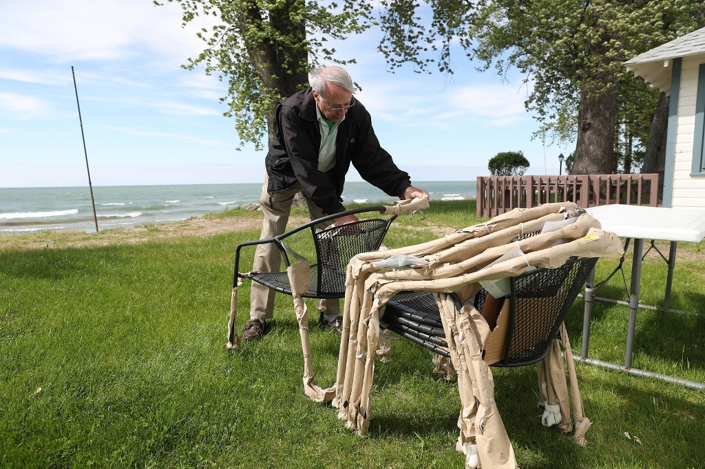 Pete Konrad brings in some new chairs for the season at the family cottage on Lake Erie. (Sharon Cantilllon/Buffalo news)