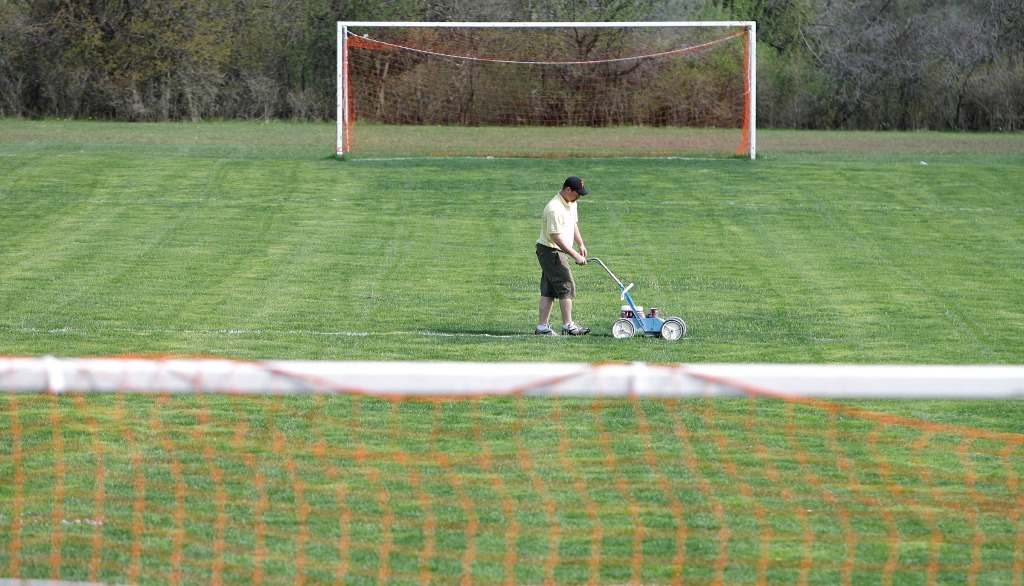 A Park School employee paints the lines on the soccer field in this file photo. (Harry Scull Jr./Buffalo News)