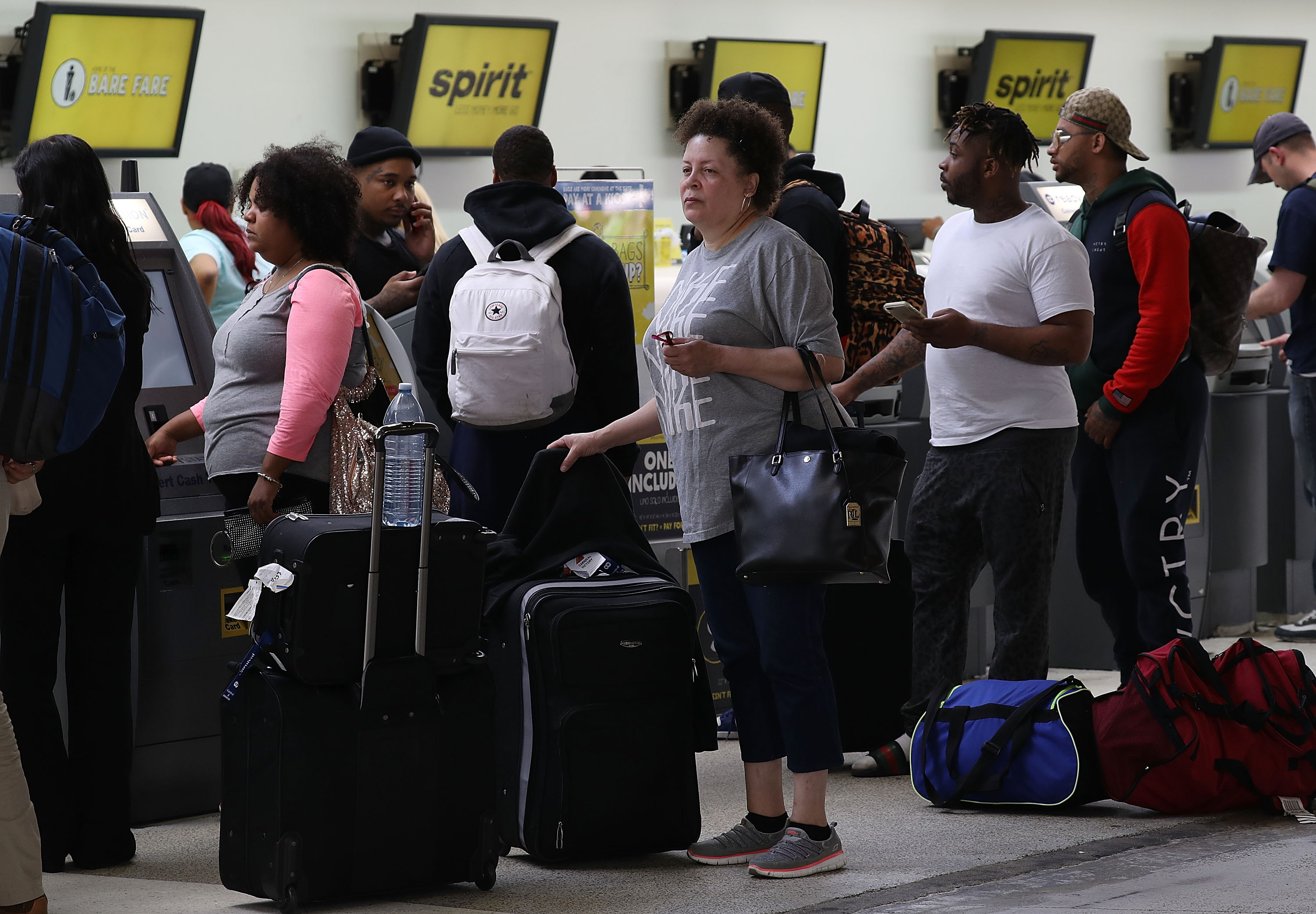 People stand in line to check in at the Spirt Airlines counter at the Fort Lauderdale-Hollywood International Airport on Tuesday in Fort Lauderdale, Fla. Yesterday a chaotic scene erupted at the Spirit Airlines counter after flights were canceled which led to passengers getting irate and the police had to move in to restore order. (Joe Raedle/Getty Images)