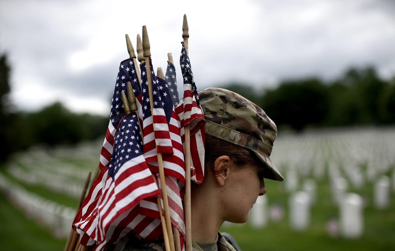 A soldier helps place flags at the headstones of veterns at Arlington National Cemetery. After years of delay, a national cemetery may soon be ready in Western New York. (Getty Images)