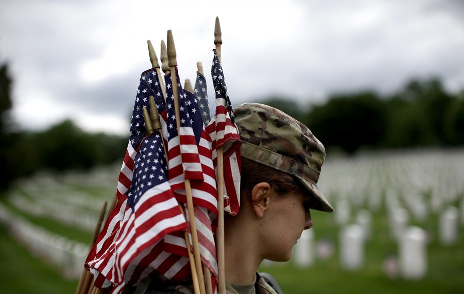 A soldier places flags at the headstones of veterans at Arlington National Cemetery in 2017. (Getty Images)