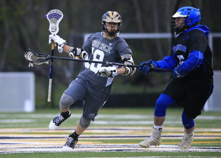 Sweet Home's Andrew Mach moves the ball against Frontier during the first half on Tuesday. The Falcons won, 15-7, with Owen Bean scoring five goals. (Photo by Harry Scull Jr. / Buffalo News)
