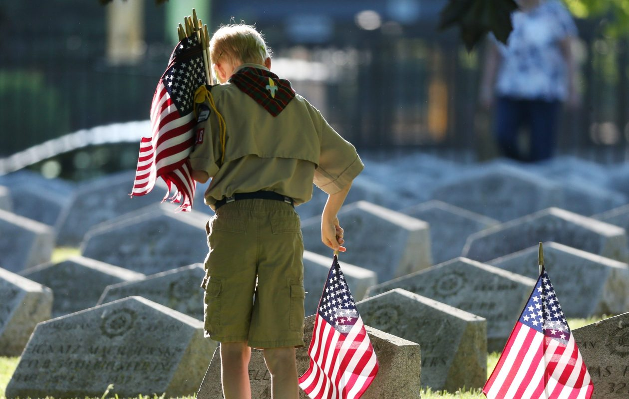 Ryan Couchman, 10, of Lancaster, was one of the volunteers who placed flags on the graves of fallen veterans to celebrate Memorial Day at Forest Lawn Cemetery in 2016. (James P. McCoy/Buffalo News)