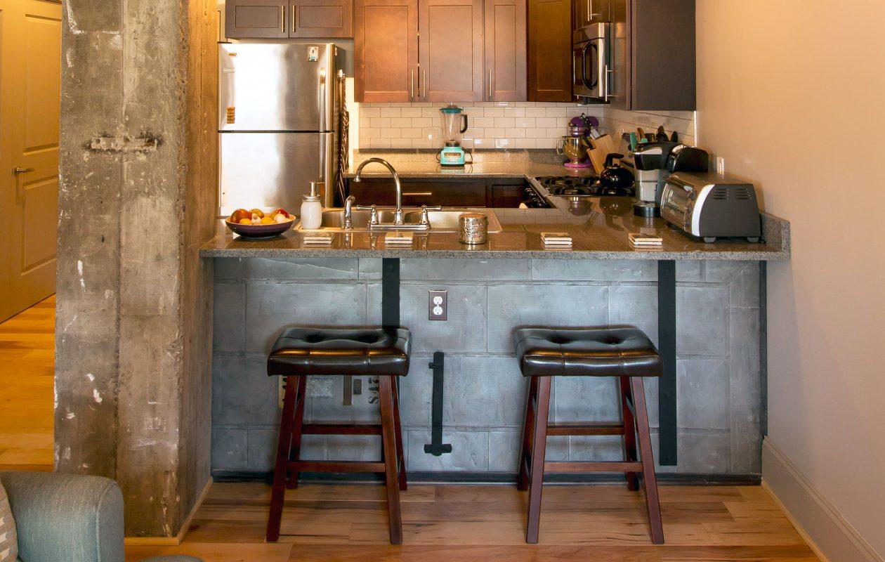 Original metal storage doors have been repurposed as the façade of the breakfast counter in Turner Bros. Lofts unit.
