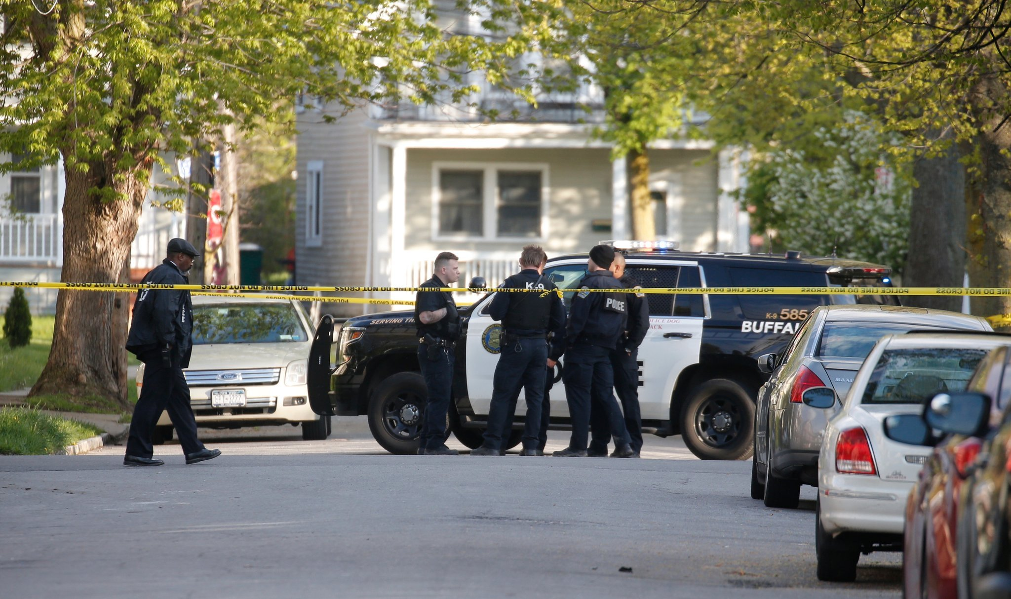 The activity at the intersection of Garfield and Hartman where a Buffalo Police officer was shot and the suspect's white SUV remained on the lawn after a chase on Sunday, May 7, 2017. (Robert Kirkham/Buffalo News)