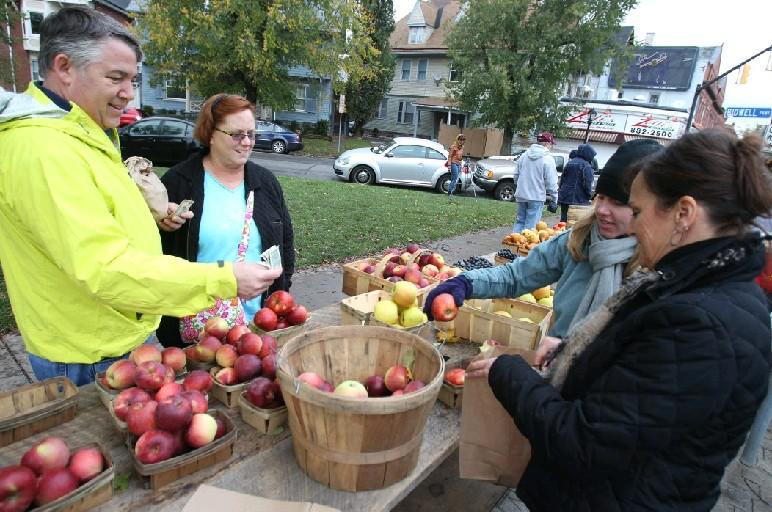 Doug and Laurie Brown buy apples from Caitlin Tyo and Cindy Nostro at the Elmwood Village Farmers Market. This year's market is down to its last two weeks. (John Hickey/News file photo)