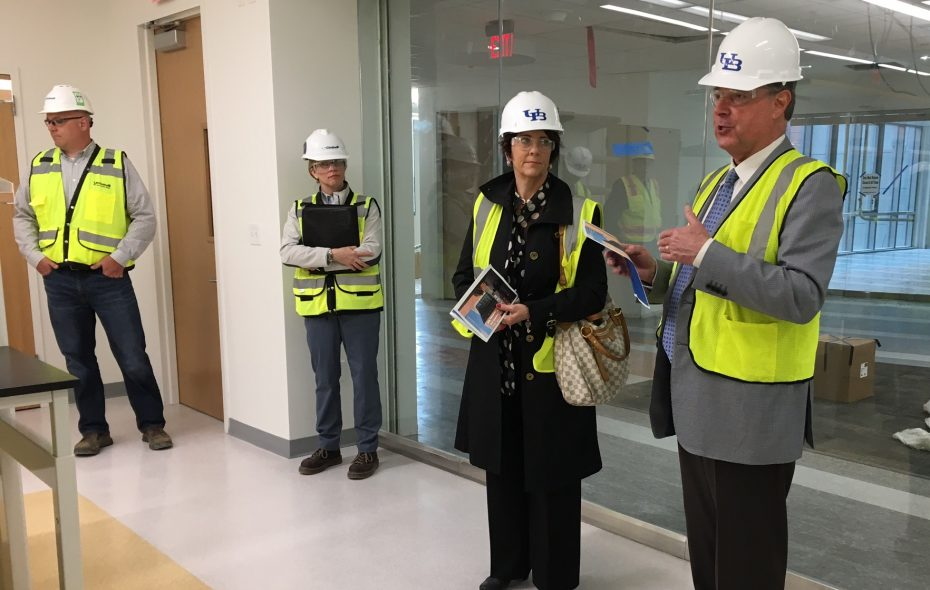 Dr. Michael E. Cain, right, dean of Jacobs School of Medicine and Biomedical Sciences, leads a tour of the new medical school building on Monday along with Nancy Paton, UB's vice president for communications. (Buffalo News)