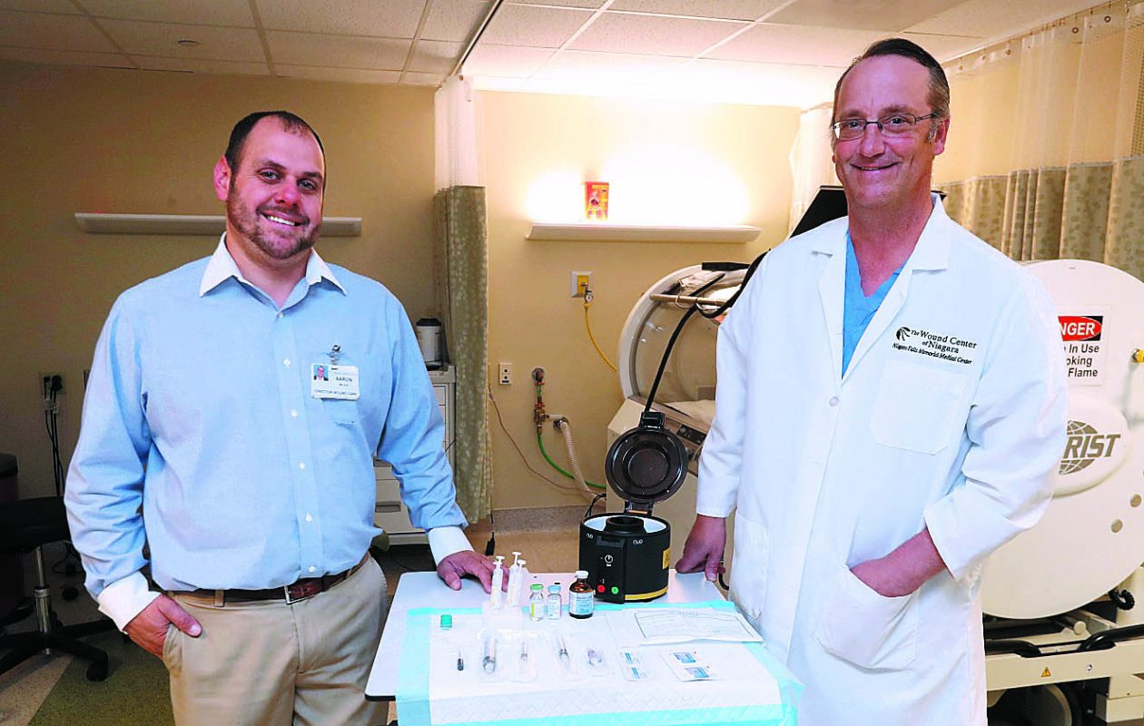"""Right now, it's a trial treatment, not a standard therapy. It's a unique trial because  it's Medicare-sponsored. It's pretty unusual for Medicare to back a study and pay for it.""  – Dr. Michael Mitchell, right, with Aaron Wilson, working with Aurix, a new device being tested  at the Wound Center of Niagara at Niagara Falls Memorial Medical Center.  (Photos by Sharon Cantillon/Buffalo News)"