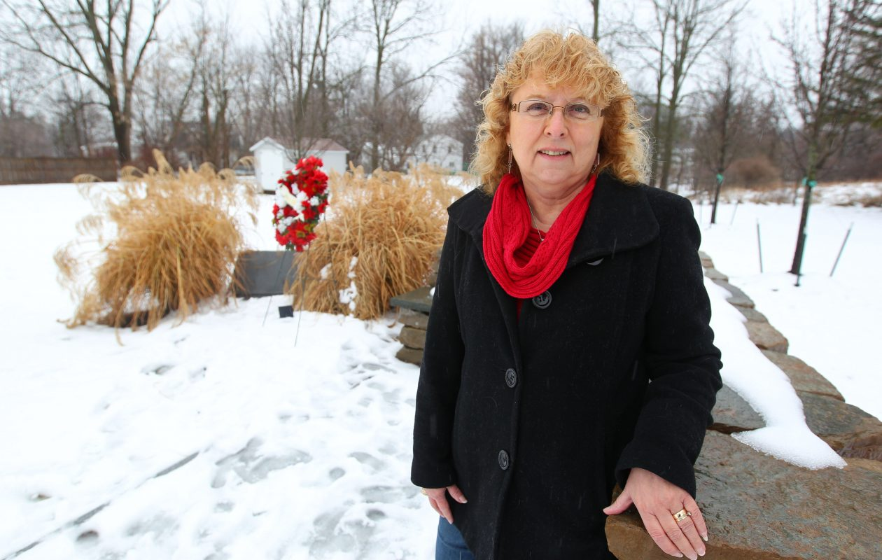 Karen Wielinski stands at the memorial to the victims of Flight 3407 and the lot where her home stood on Long Street in Clarence Center on Tuesday, Feb. 7, 2017.         (Mark Mulville/Buffalo News)