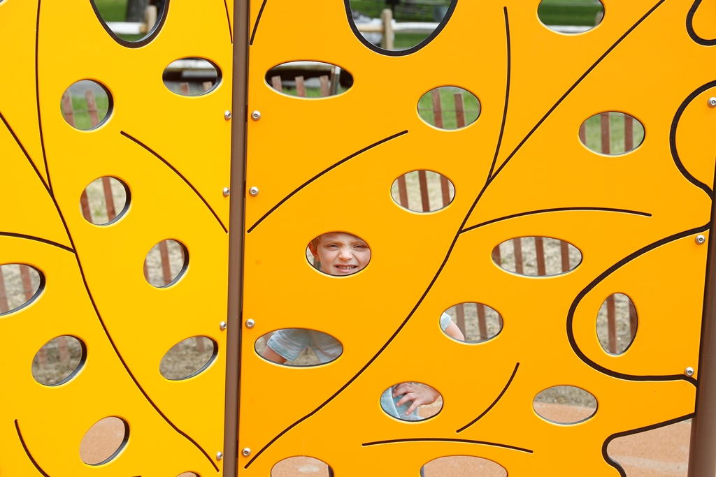 Chase Kinsley , 4, peeks through the custom-made leaf-shaped climbing wall at the new DeVeaux Woods State Park playground. (John Hickey/Buffalo News)