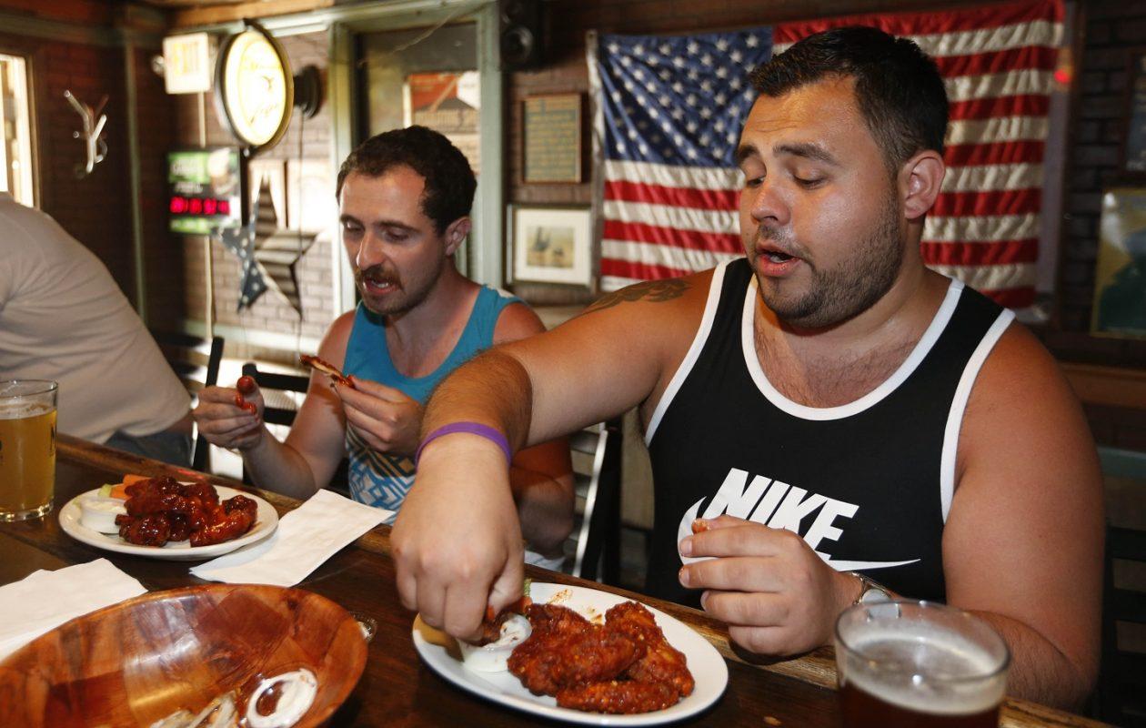 Mike Bueme, left, of Cheektowaga, enjoys the BBQ hot wings while Corey Spruce of Blasdell has the extra hot garlic wings. (Sharon Cantillon/Buffalo News)
