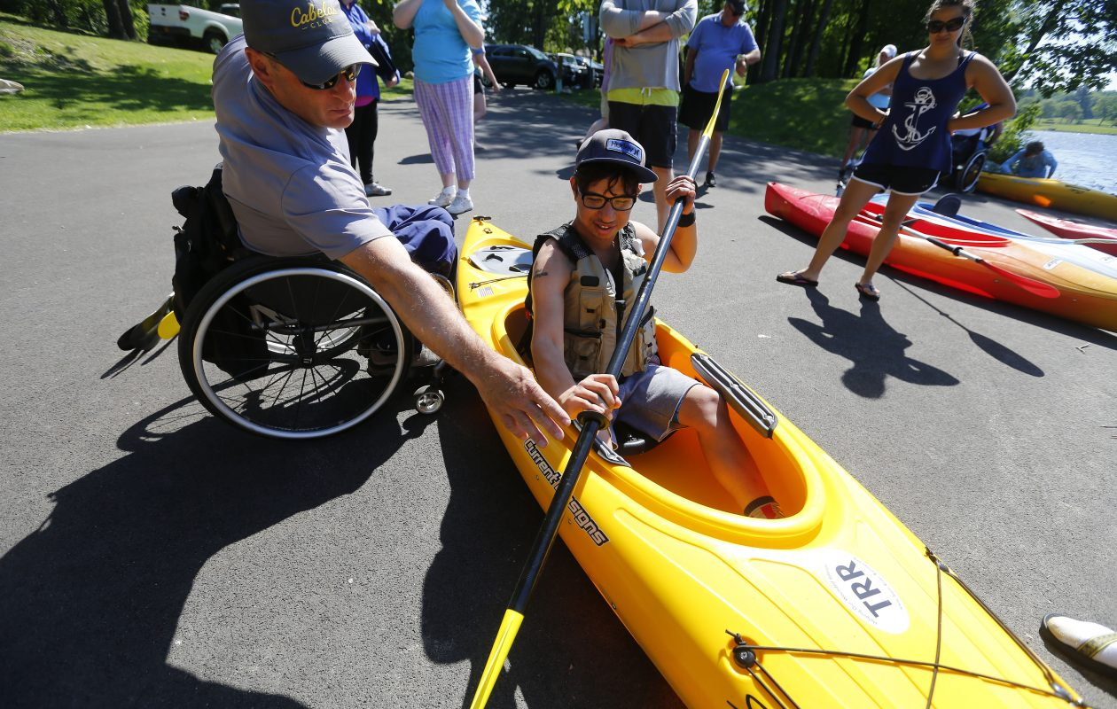 Steve Spitz, left, gives a paddling lesson to Ilya Svec as WNY Adaptive Water Sports and Orchard Park Recreation present Team River Runner Adaptive Kayaking, where people with disabilities can come down and learn to kayak at Green Lake in Orchard Park on Sunday, June 11, 2017. (Mark Mulville/Buffalo News)